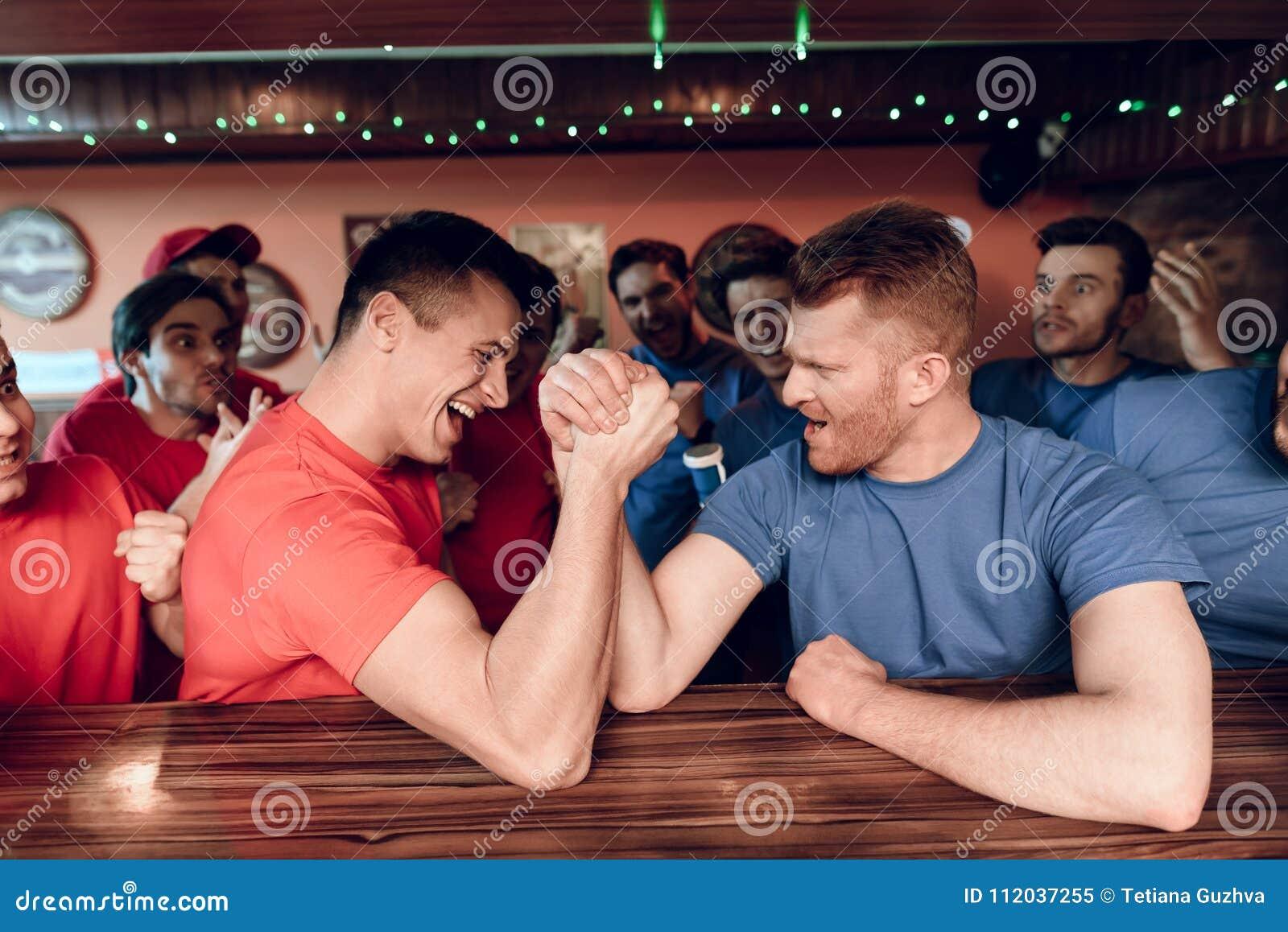 Błękita i czerwieni drużyna wachluje ręki zapaśnictwo przy sporta barem z fan w tle