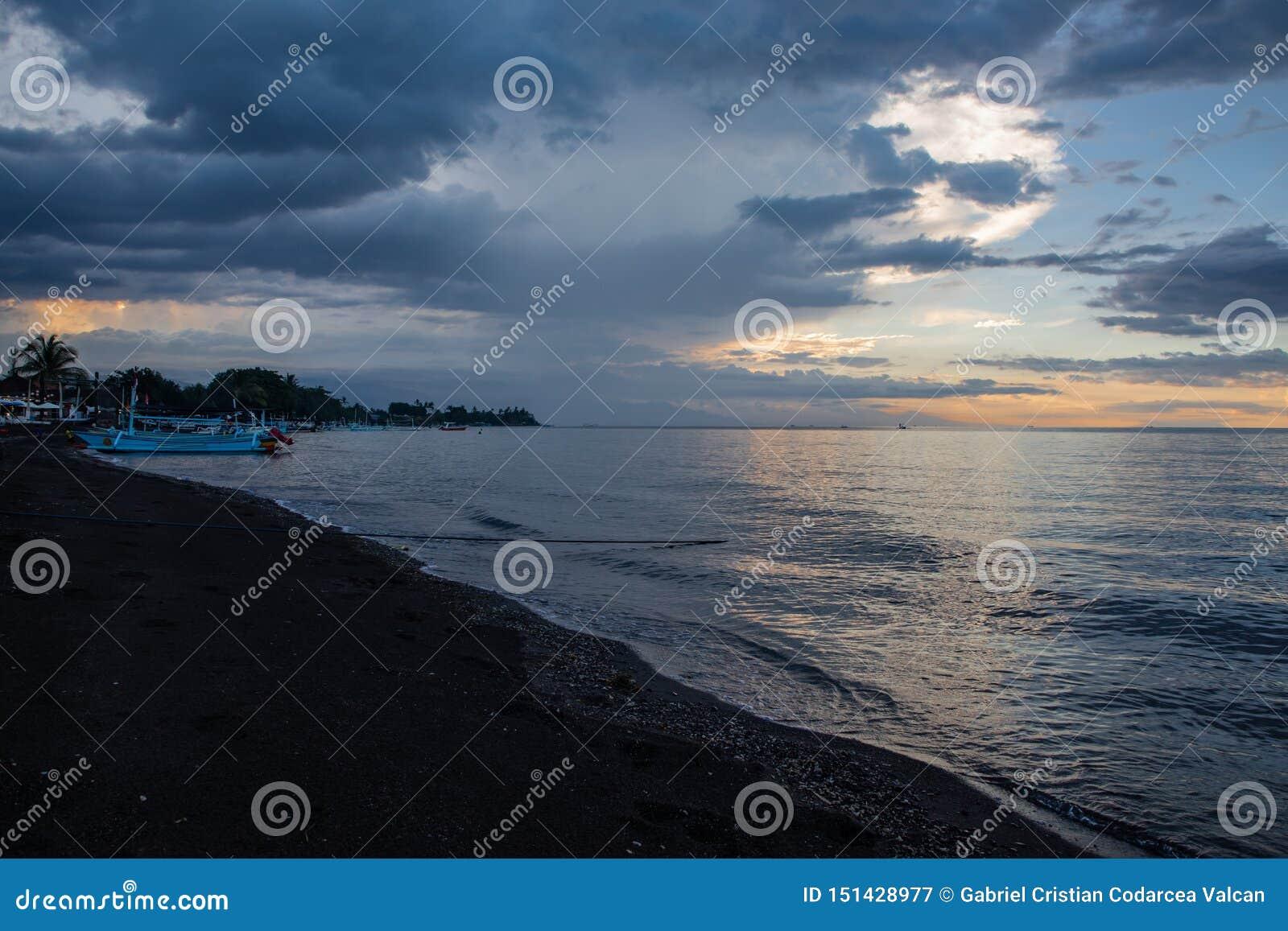 Błękitna godzina nad spokojnym oceanem i czarny piasek wyrzucać na brzeg z balijczyk łodzią