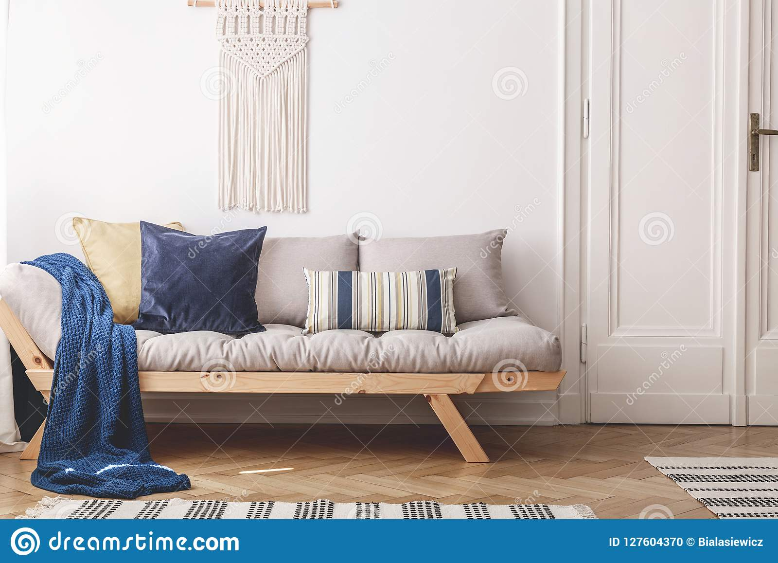 Błękitna koc i poduszki na beżowej drewnianej kanapie w białym loft wnętrzu z drzwi Istna fotografia
