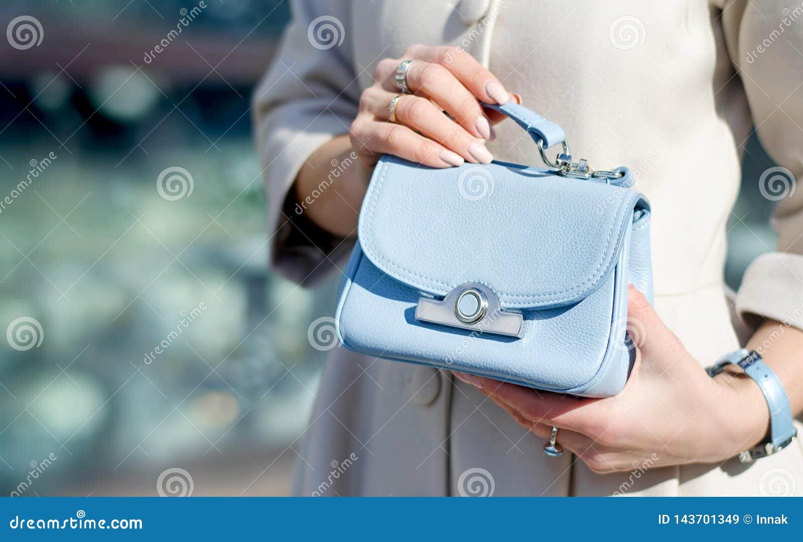 Błękitna mała torebka w żeńskich rękach W górę rzemiennej torebki Kobiety chodzi w mie?cie Dziewczyna w be?owym ?akiecie