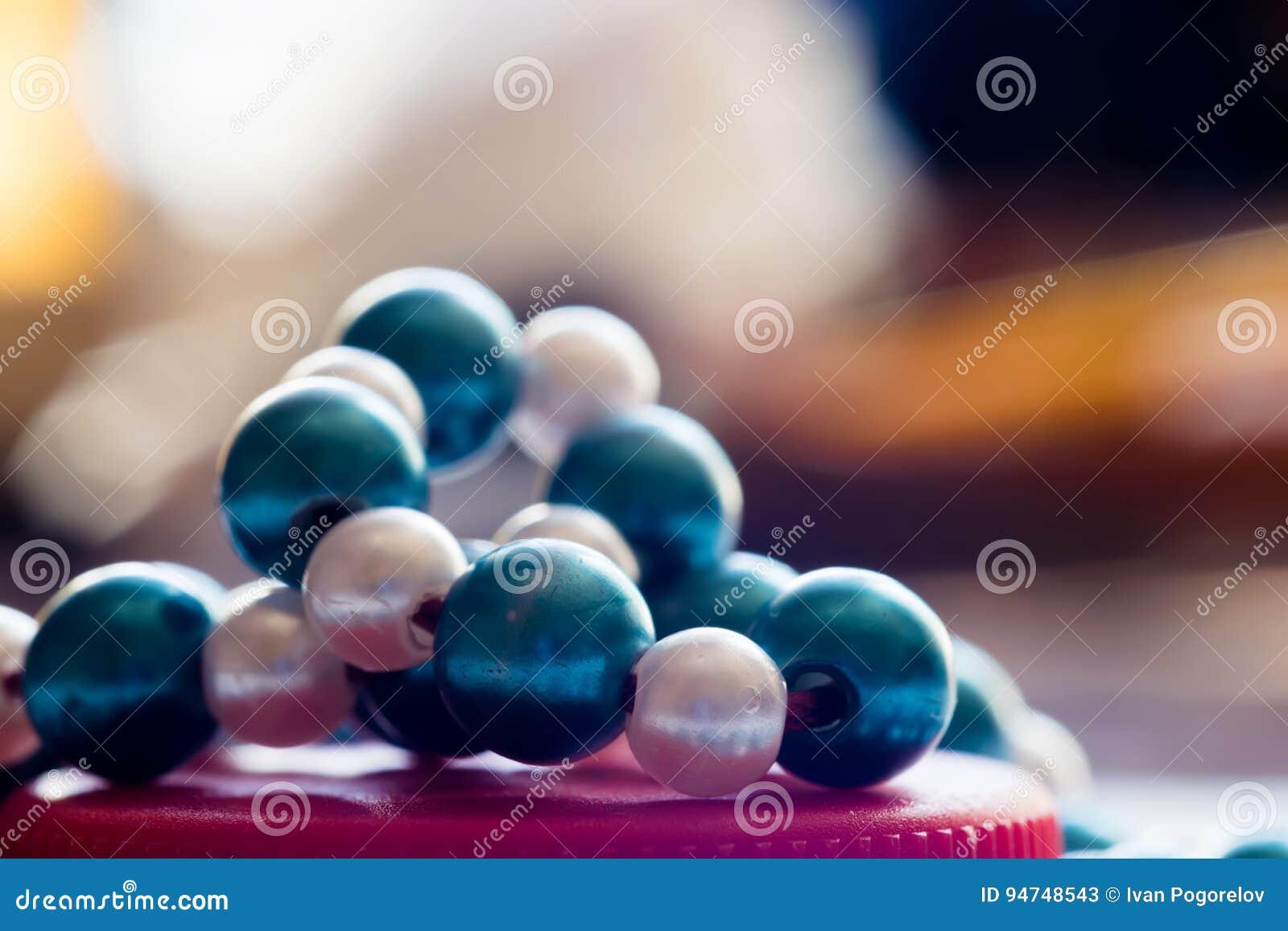 Błękitni i biali koraliki na czerwieni zawiązują kolorowe tło Makro-