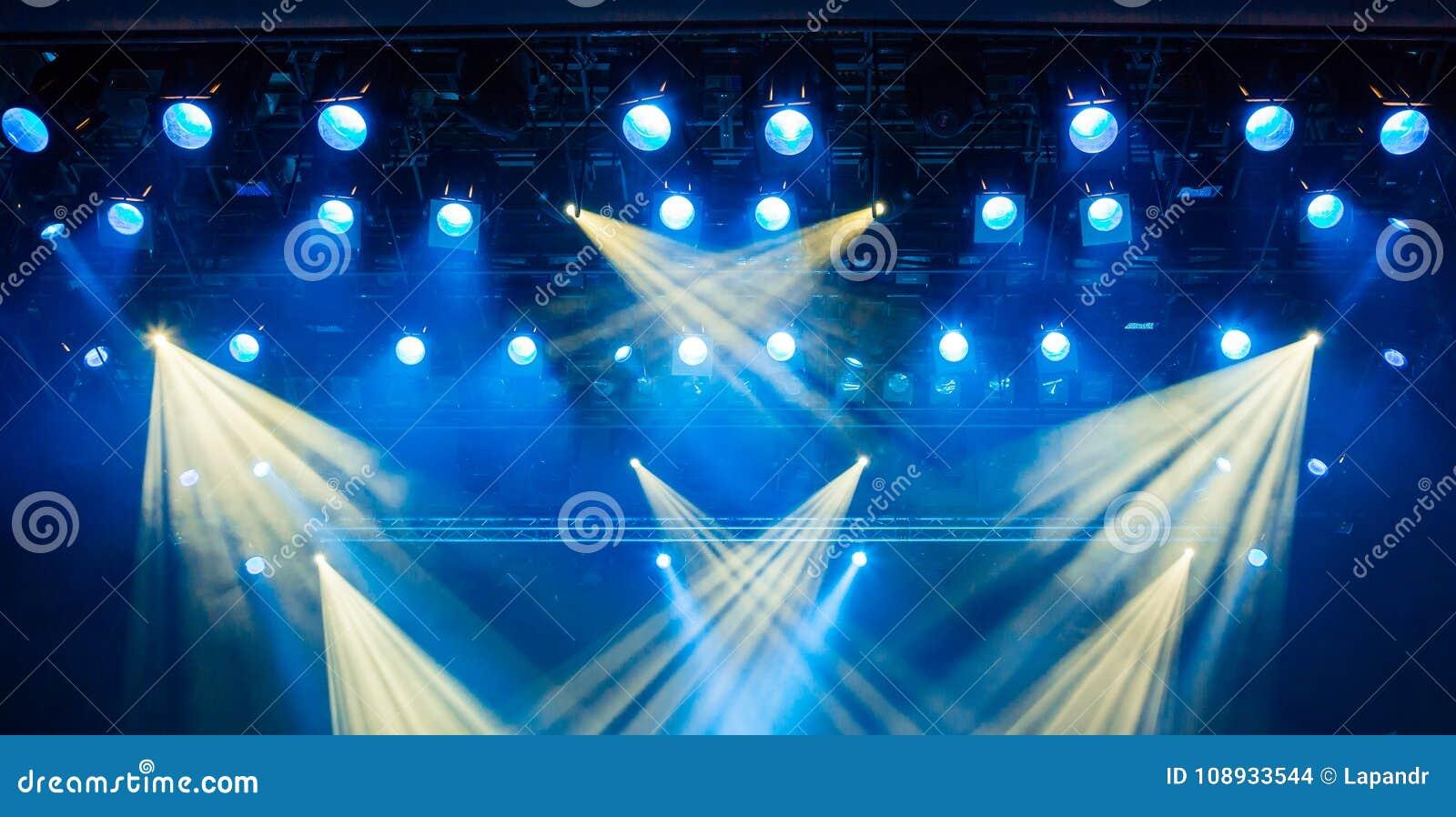 Błękitni lekcy promienie od światła reflektorów przez dymu przy filharmonią lub teatrem Oświetleniowy wyposażenie dla przedstawie
