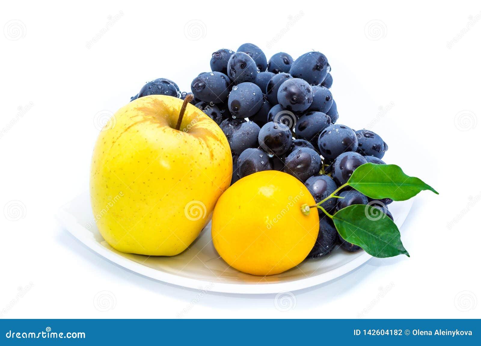 Błękitni winogrona z żółtym jabłkiem i cytryną na białym talerzu