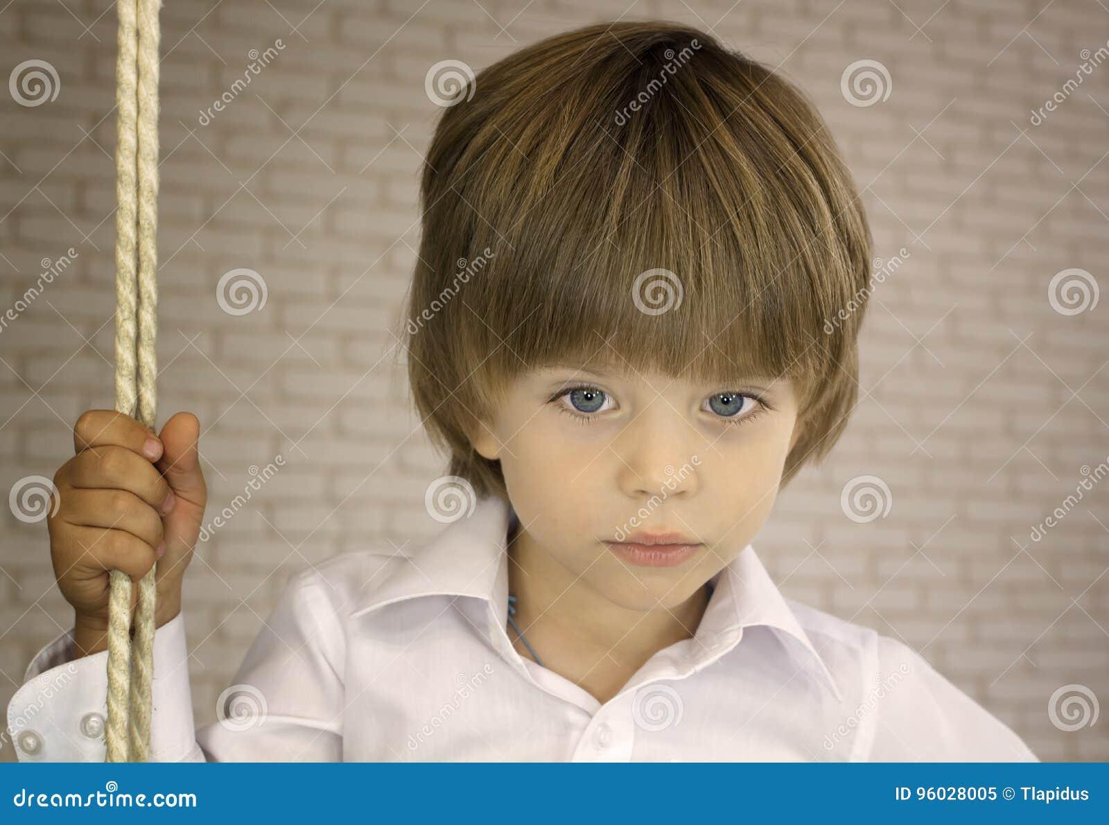 Błękitnooka chłopiec w białej koszula z arkaną