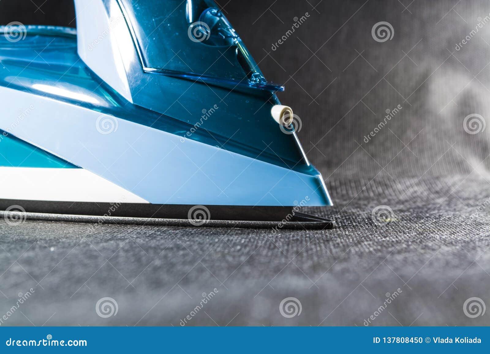 Błękitny żelazo dla odprasowywać odziewa Monophonic czarny tło gospodarstw domowych urządzenia elektronika nowożytne technologie