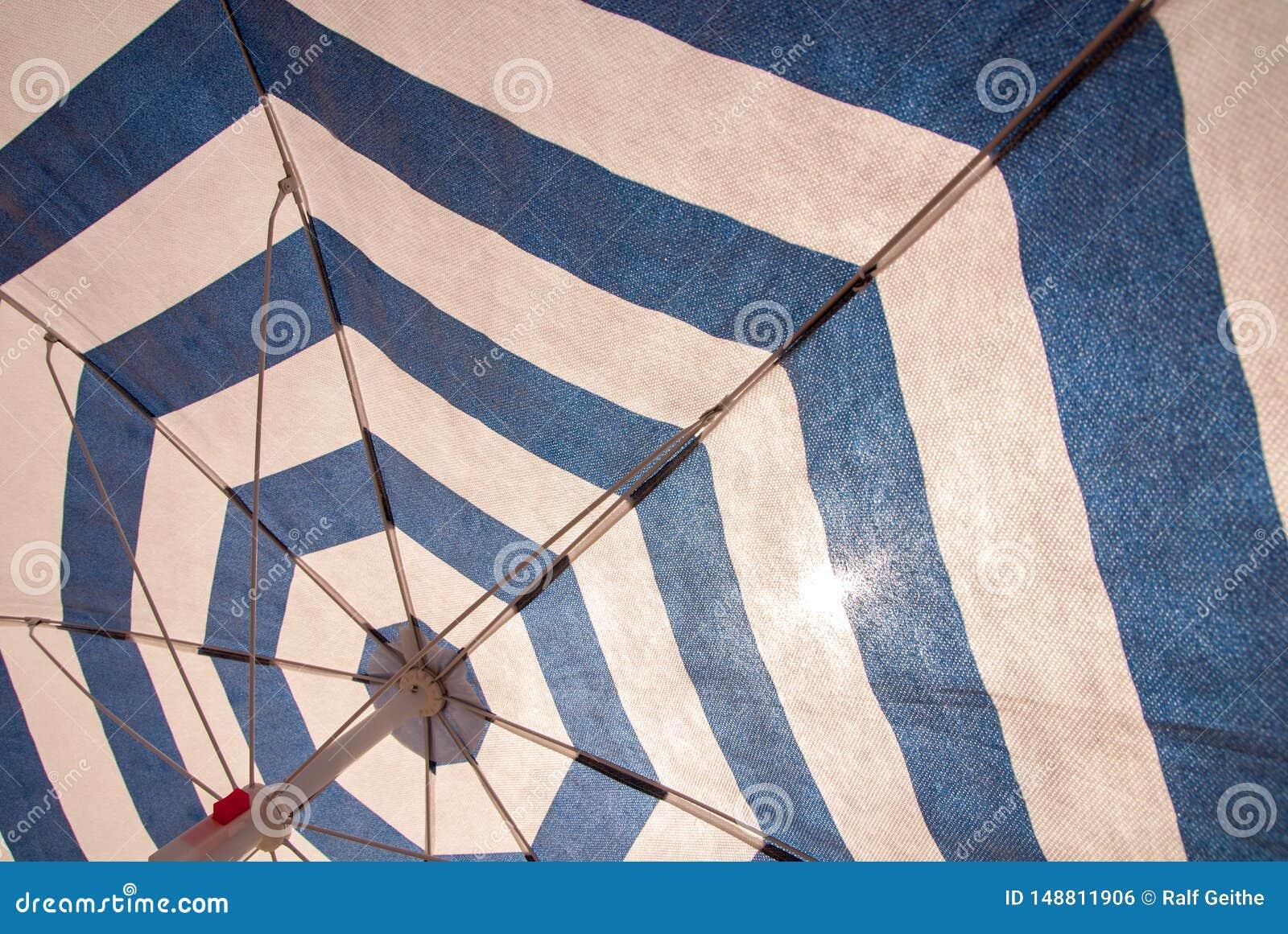 Błękitny biały parasol jako tło