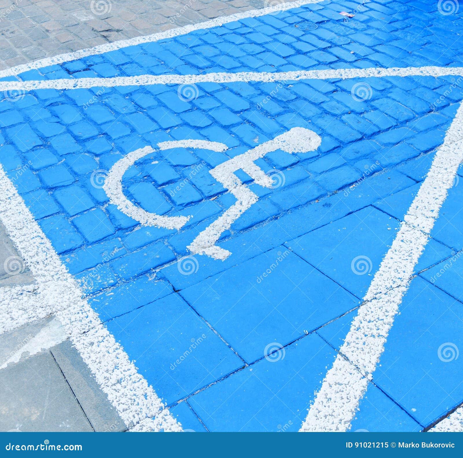 Błękitny foru parking znak na asfalcie dla persons z kalectwem
