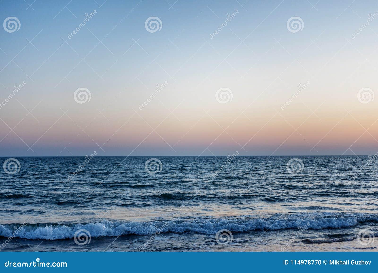 Błękitny morze przy zmierzchem fala są brzeg Nad horyzontem słońce