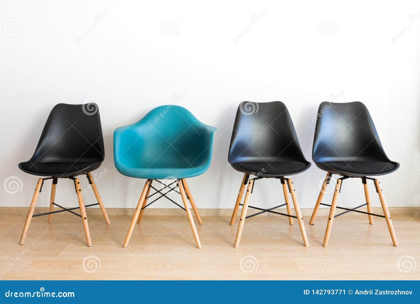 Błękitny wygodny krzesło wśród czerni