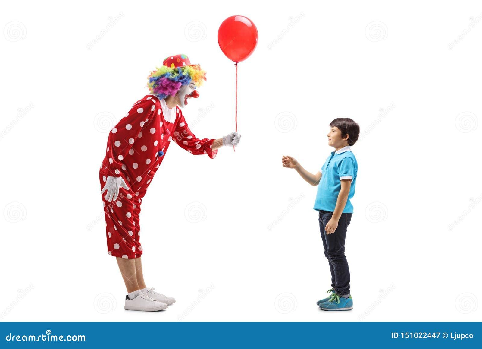 Błazen daje czerwonemu balonowi chłopiec