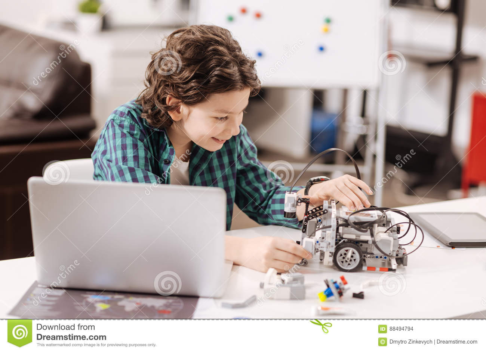 Błoga chłopiec używa nowożytnych przyrząda w nauki studiu