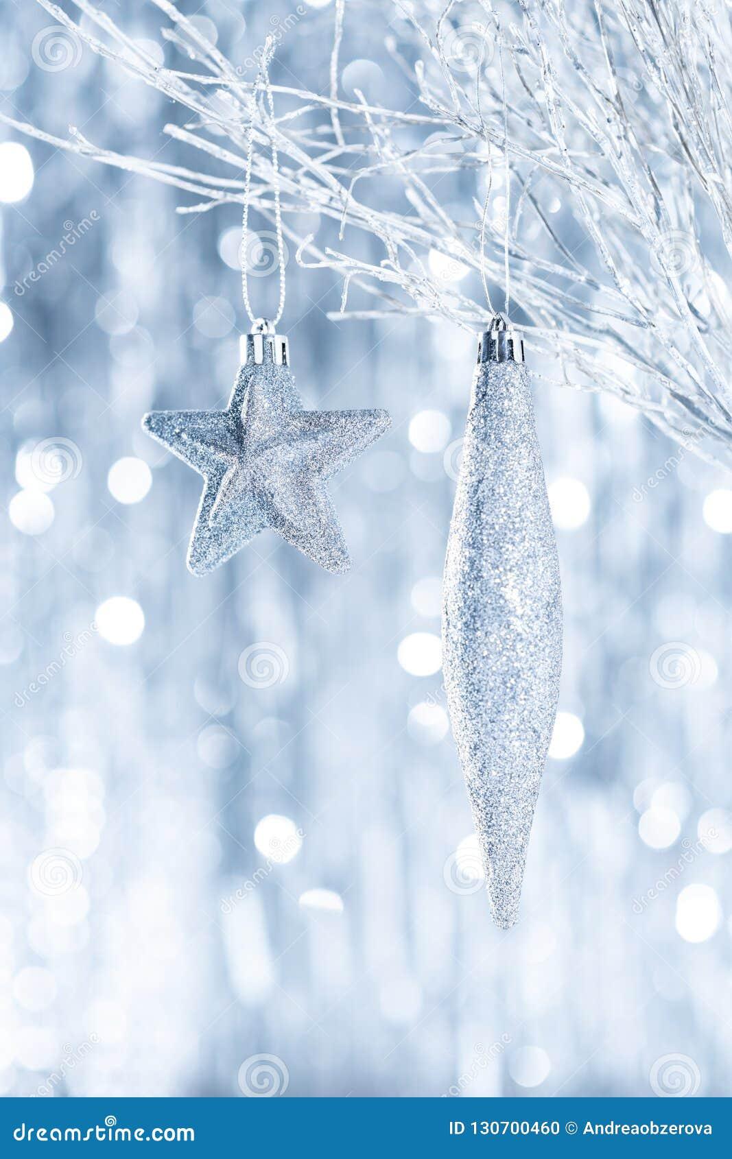 Błyszczący srebni boże narodzenia ornamentują obwieszenie na drzewie z defocused bożonarodzeniowymi światłami,