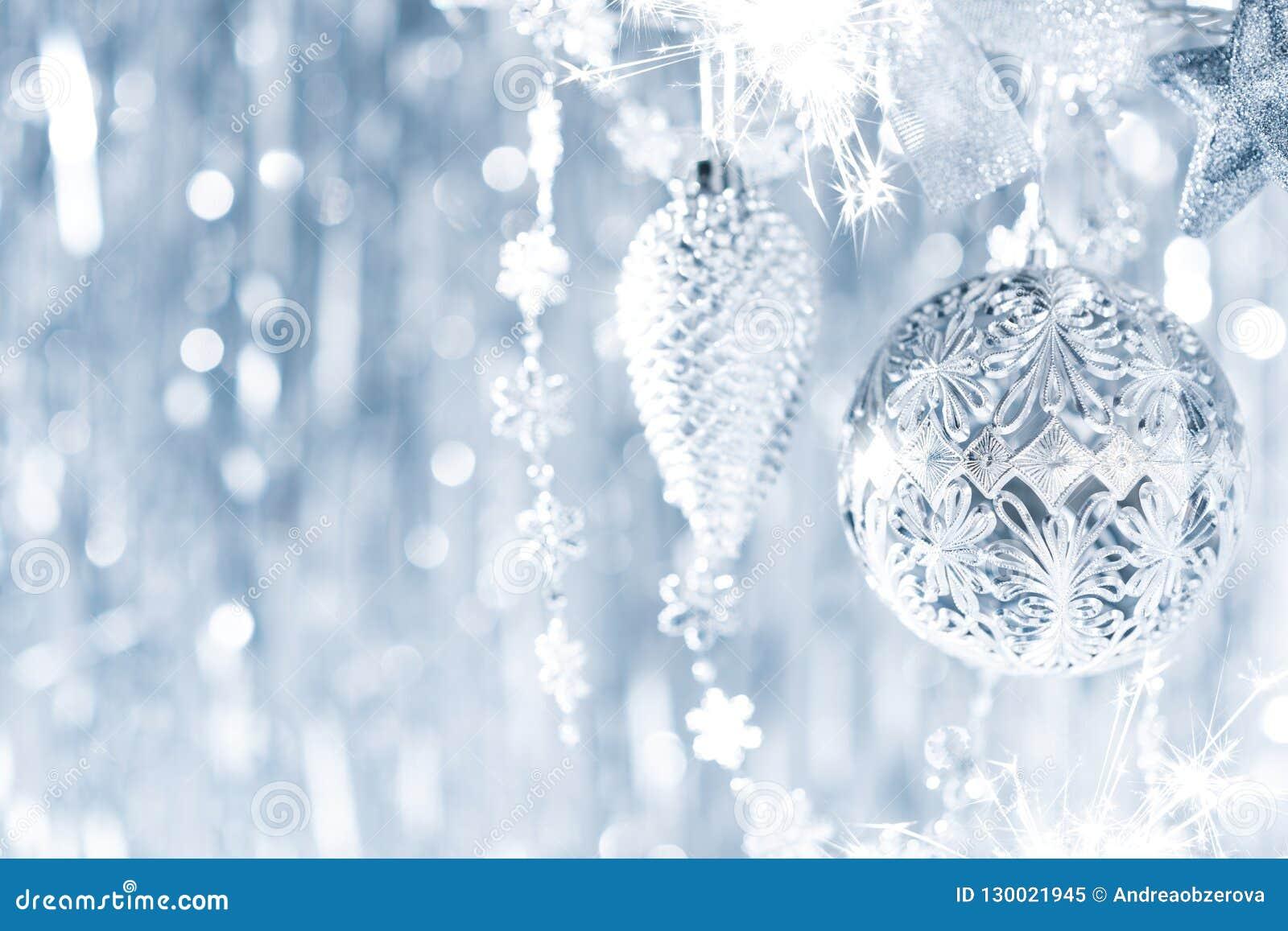 Błyszczący srebni boże narodzenia ornamentują obwieszenie na drzewie z defocused bożonarodzeniowymi światłami w tle, abstrakcjoni