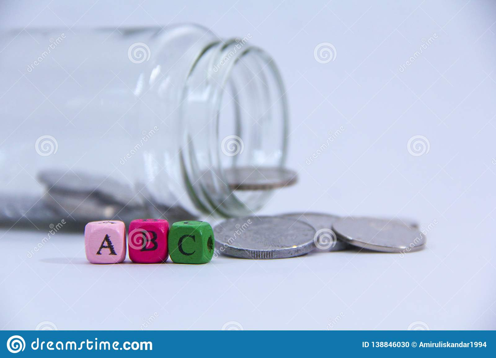 A,B and C in wooden block with coin at the back