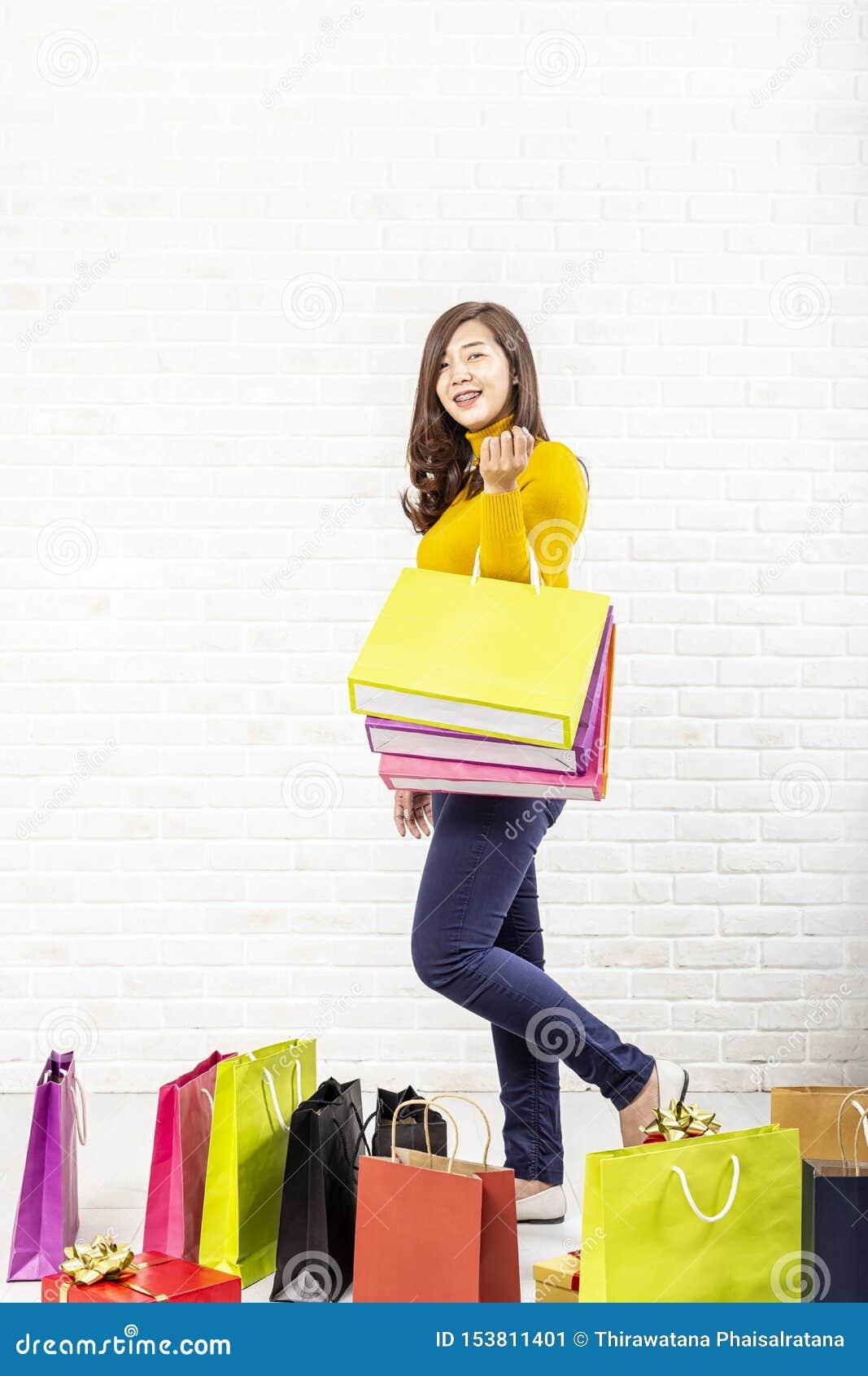 B?rande shoppingp?sar f?r h?rlig asiatisk flicka bakgrund som isoleras ?ver le vit kvinna f?r shopping asiatisk h?rlig flicka ung