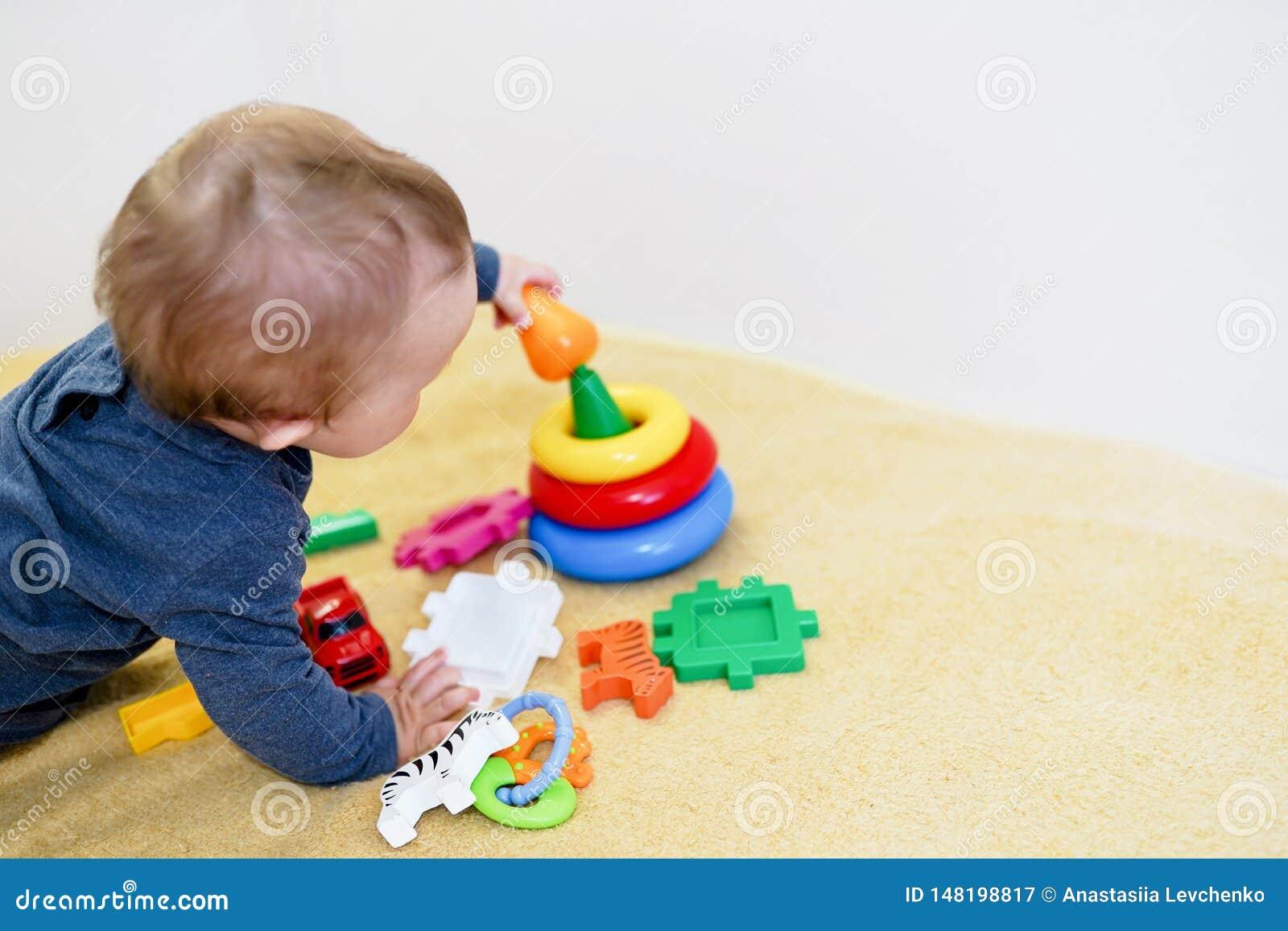 B?b? smilling et jouant avec les jouets color?s ? la maison fond d enfant avec l espace de copie D?veloppement pr?coce pour des e