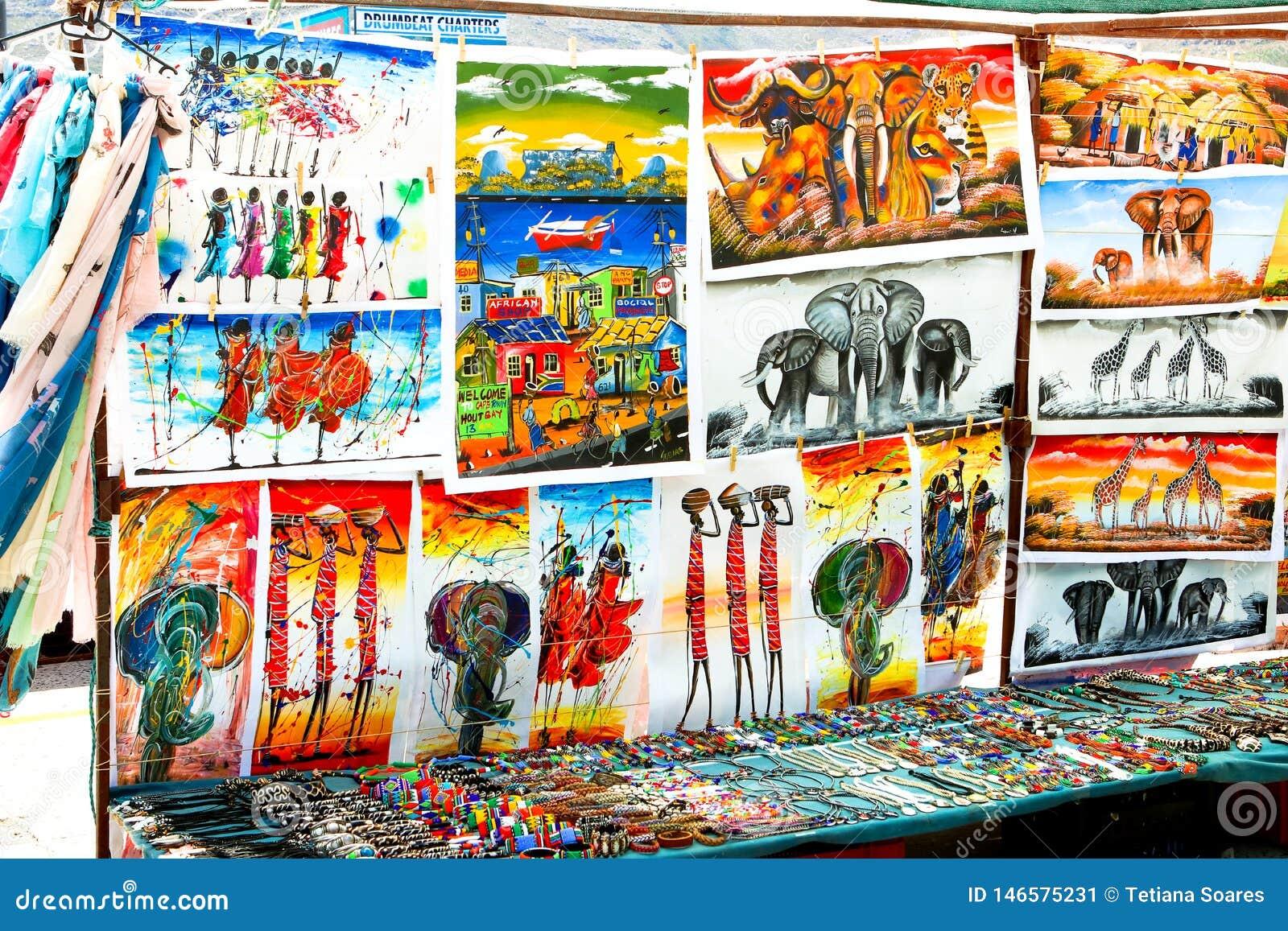 BAÍA DE HOUT, CAPE TOWN, ÁFRICA DO SUL - 24 DE DEZEMBRO DE 2017: Pinturas africanas tradicionais, acessórios feitos a mão e lembr
