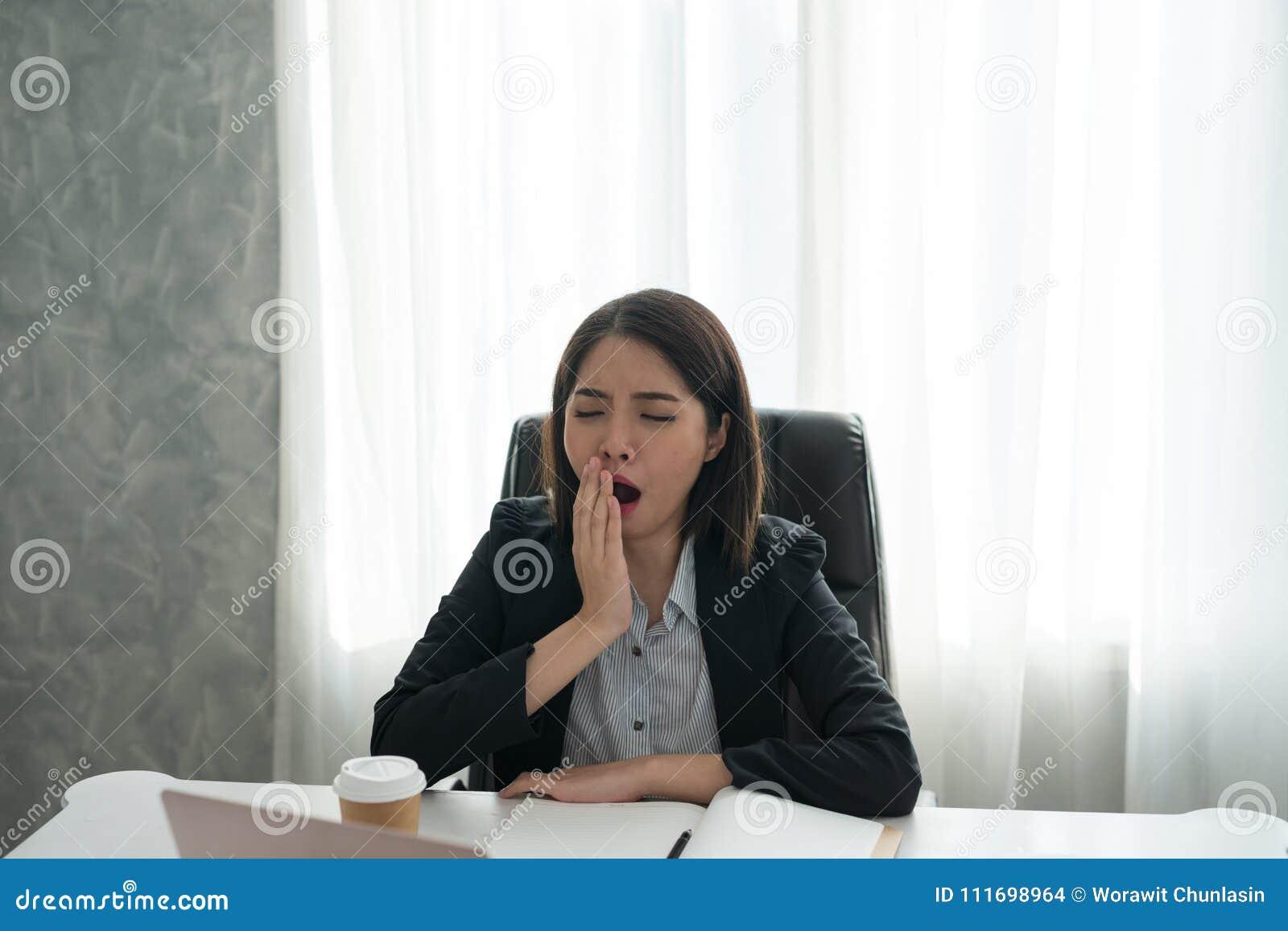 Baîllement somnolent de jeune fille asiatique d affaires avec le travail au bureau