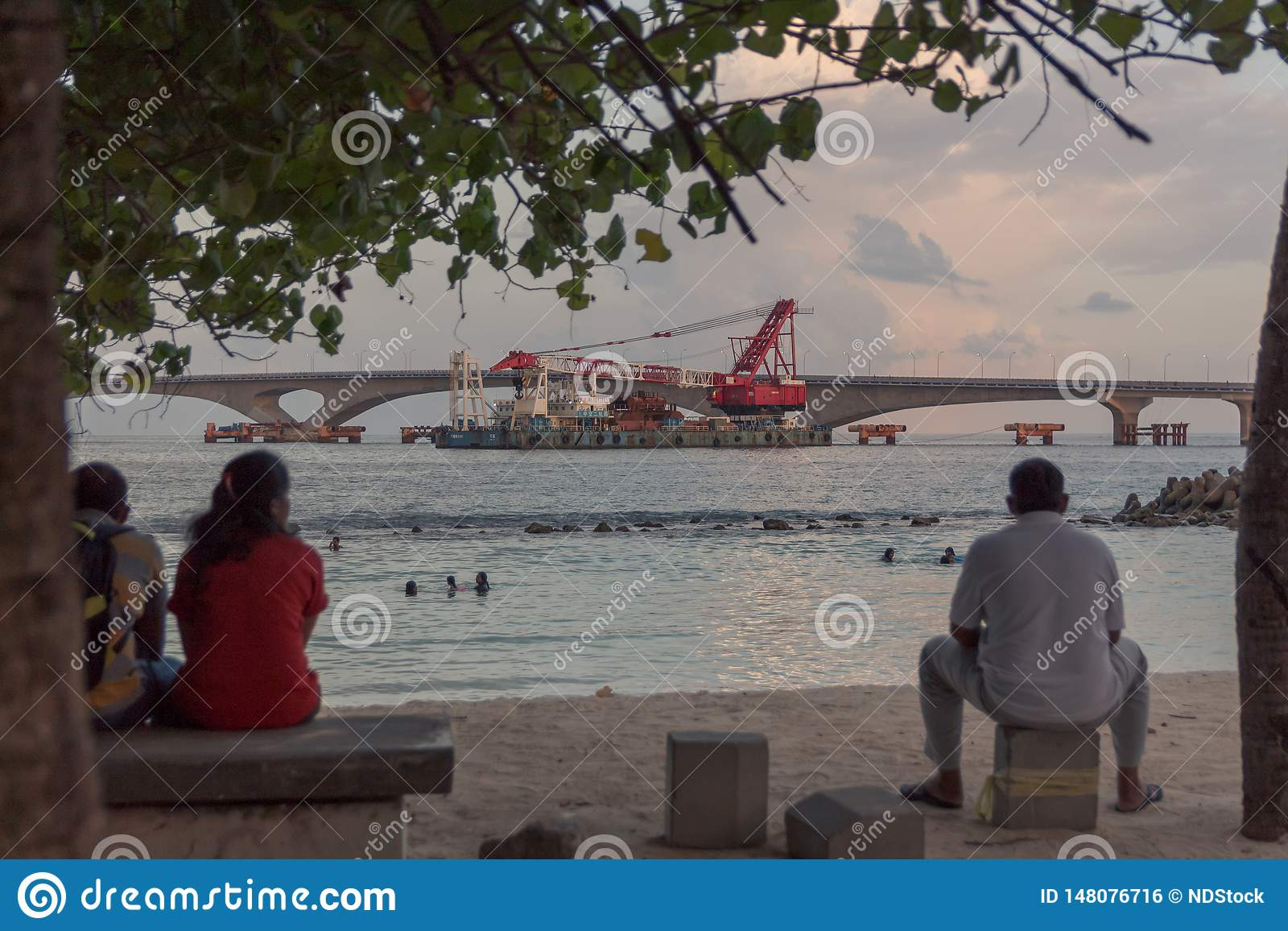 Bañistas asentados y de observaciones en una pequeña playa en varón, Maldivas de la gente
