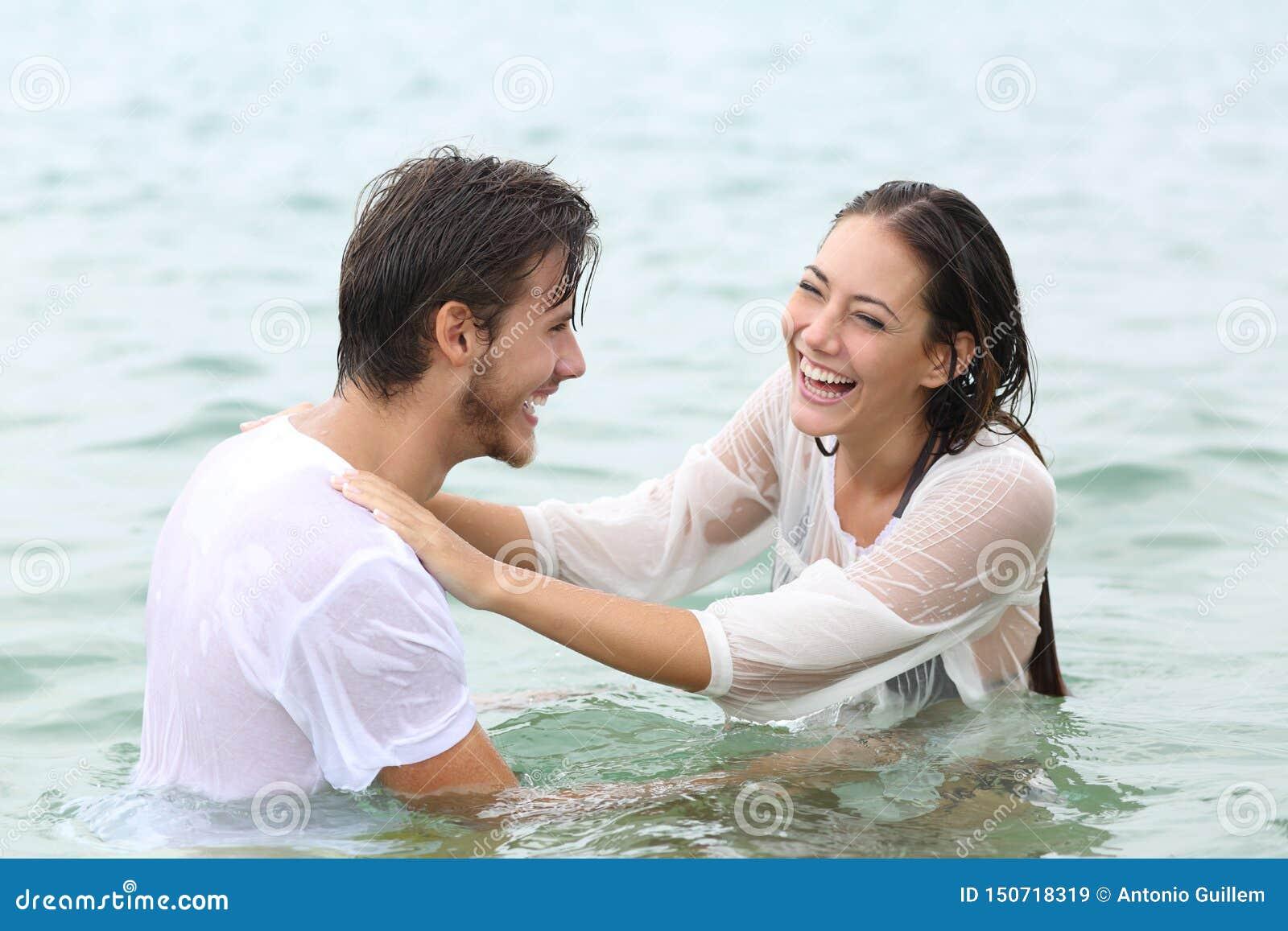 Baño humorístico de los pares divertidos en la playa