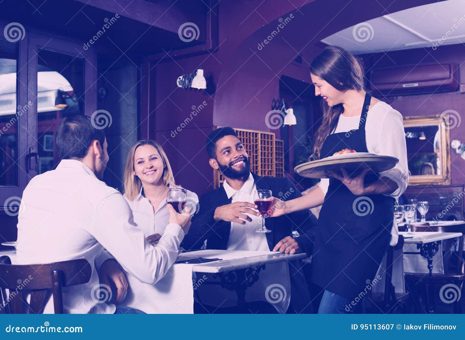 Babbelende volwassenen en vrolijke serveerster