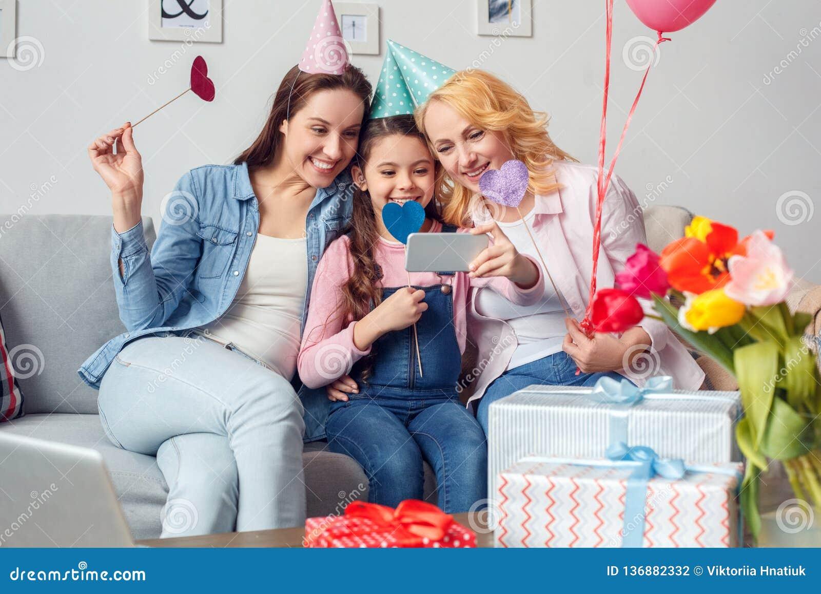 Babci córki wpólnie w domu i matki świętowania obsiadanie w świątecznych nakrętkach ściska z brać selfie fotografie