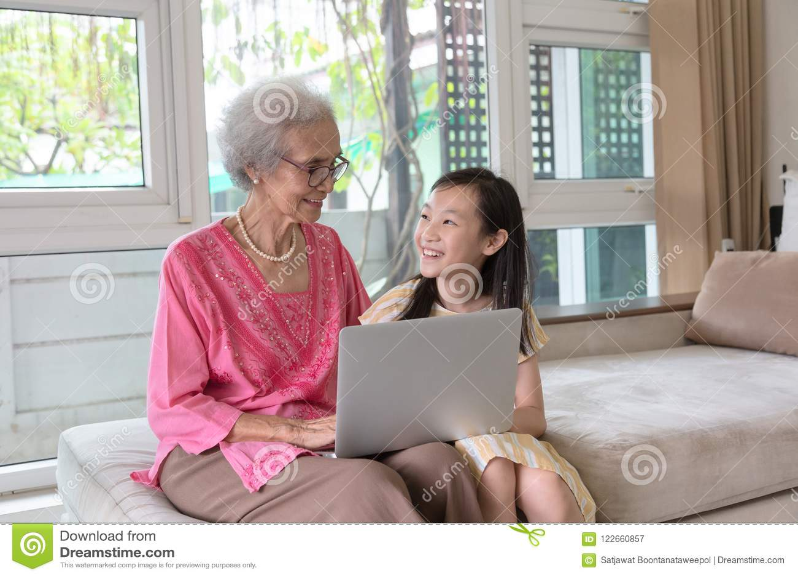Babcia i wnuczka używa laptop i obsiadanie