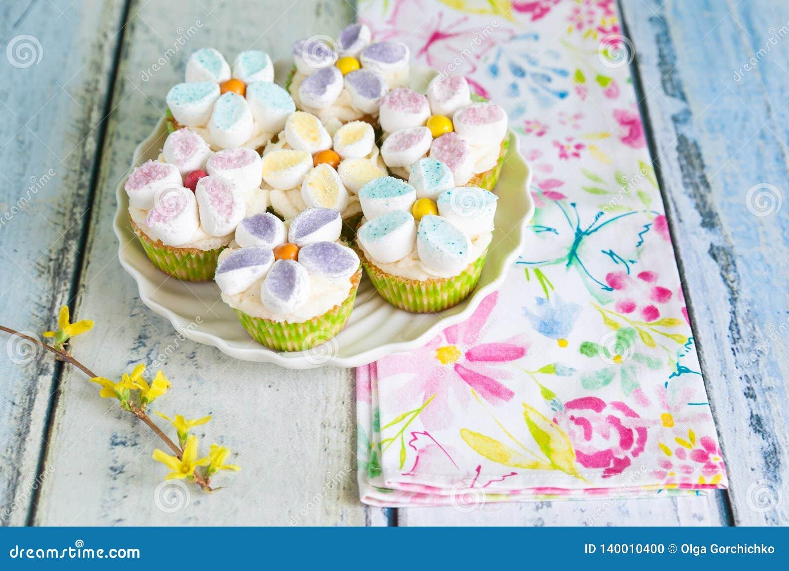Babeczki dekorować z masła marshmallow i śmietanki kwiatami