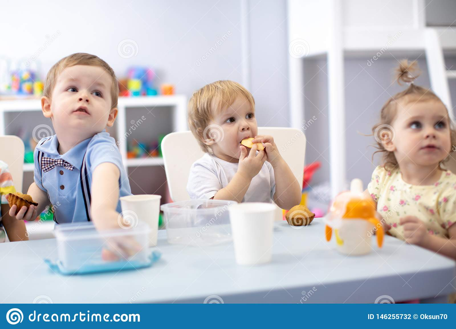 Babies children eating healthy food in nursery or kindergarten