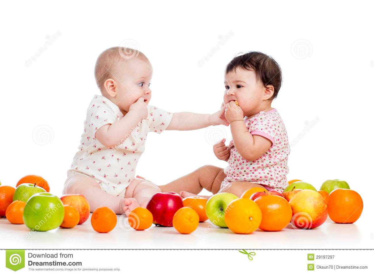 Babies girls eating healthy food fruits on white