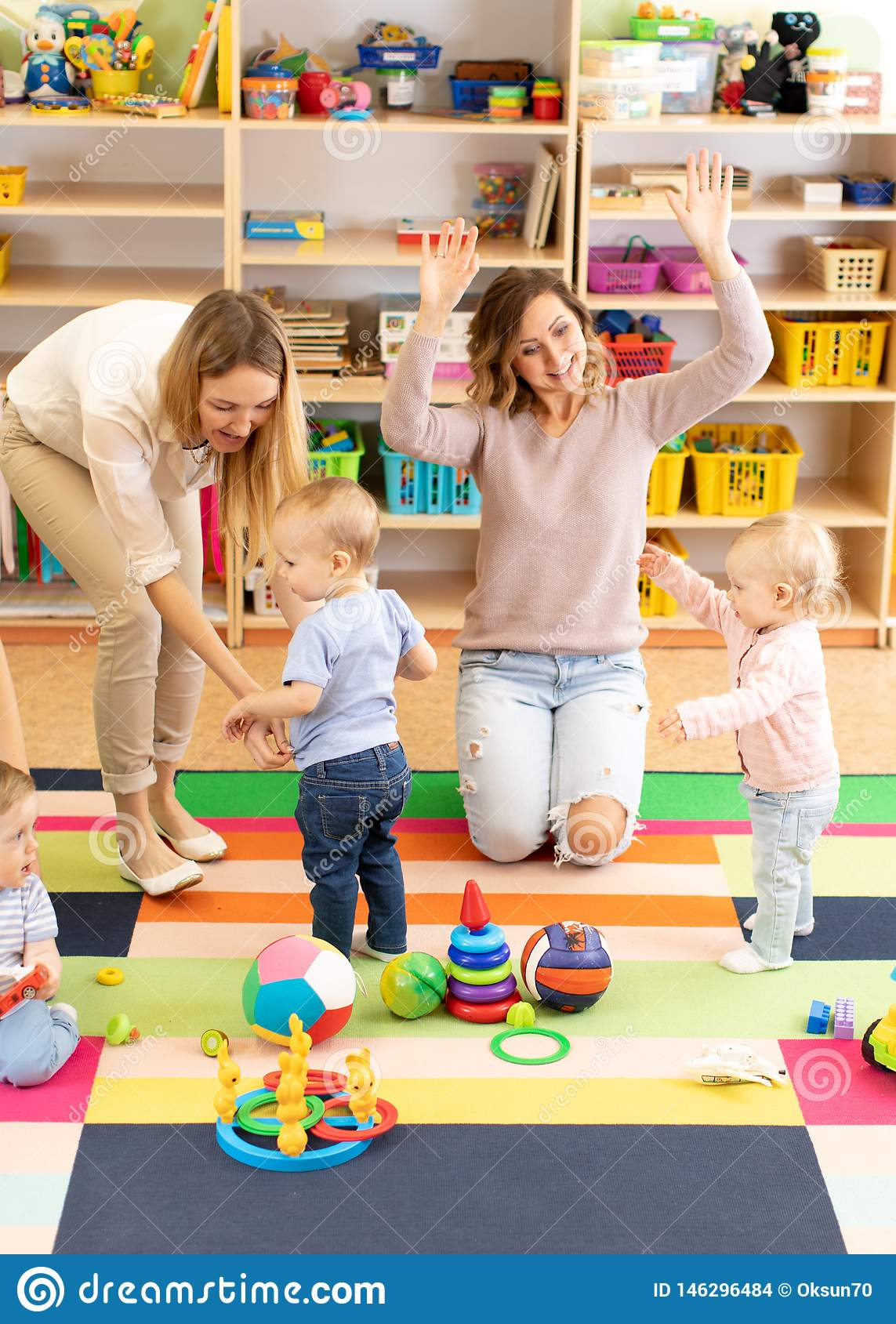Babies toddlers playing with colorful educational toys together with mothers in nursery room