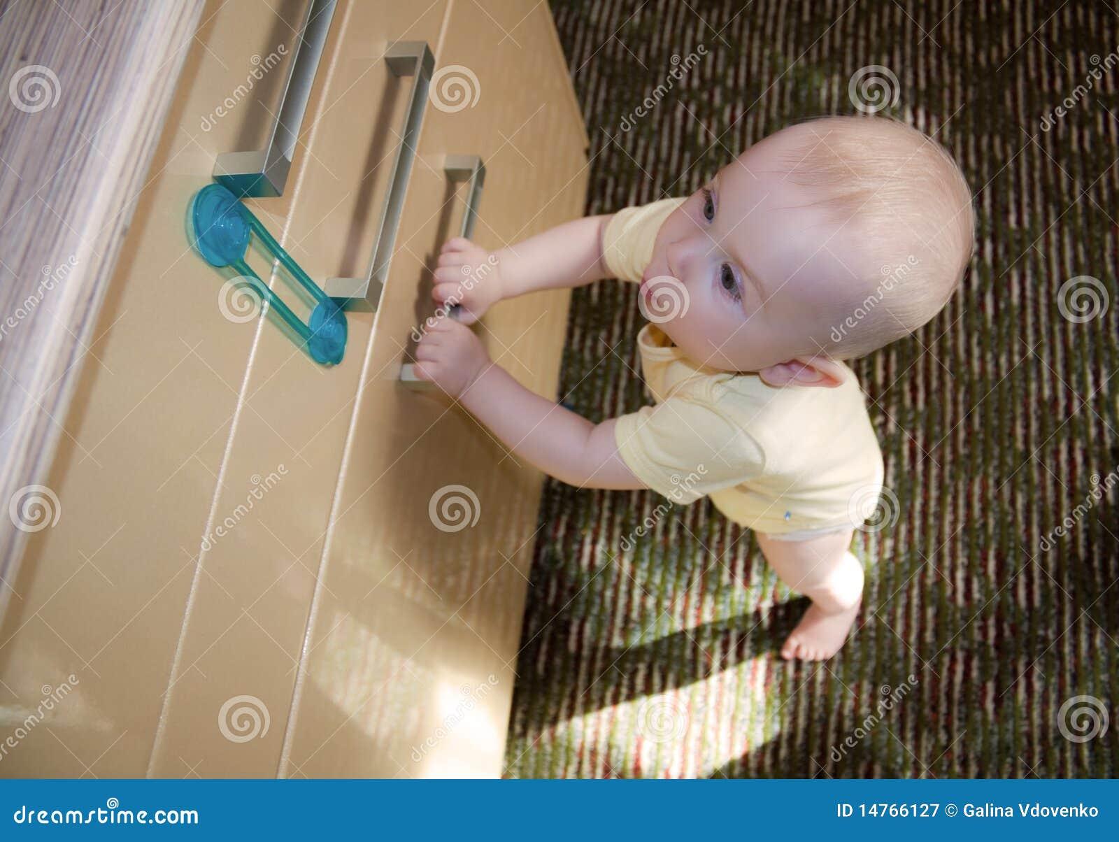 Baby 8-9 maanden die de deurkast proberen te openen