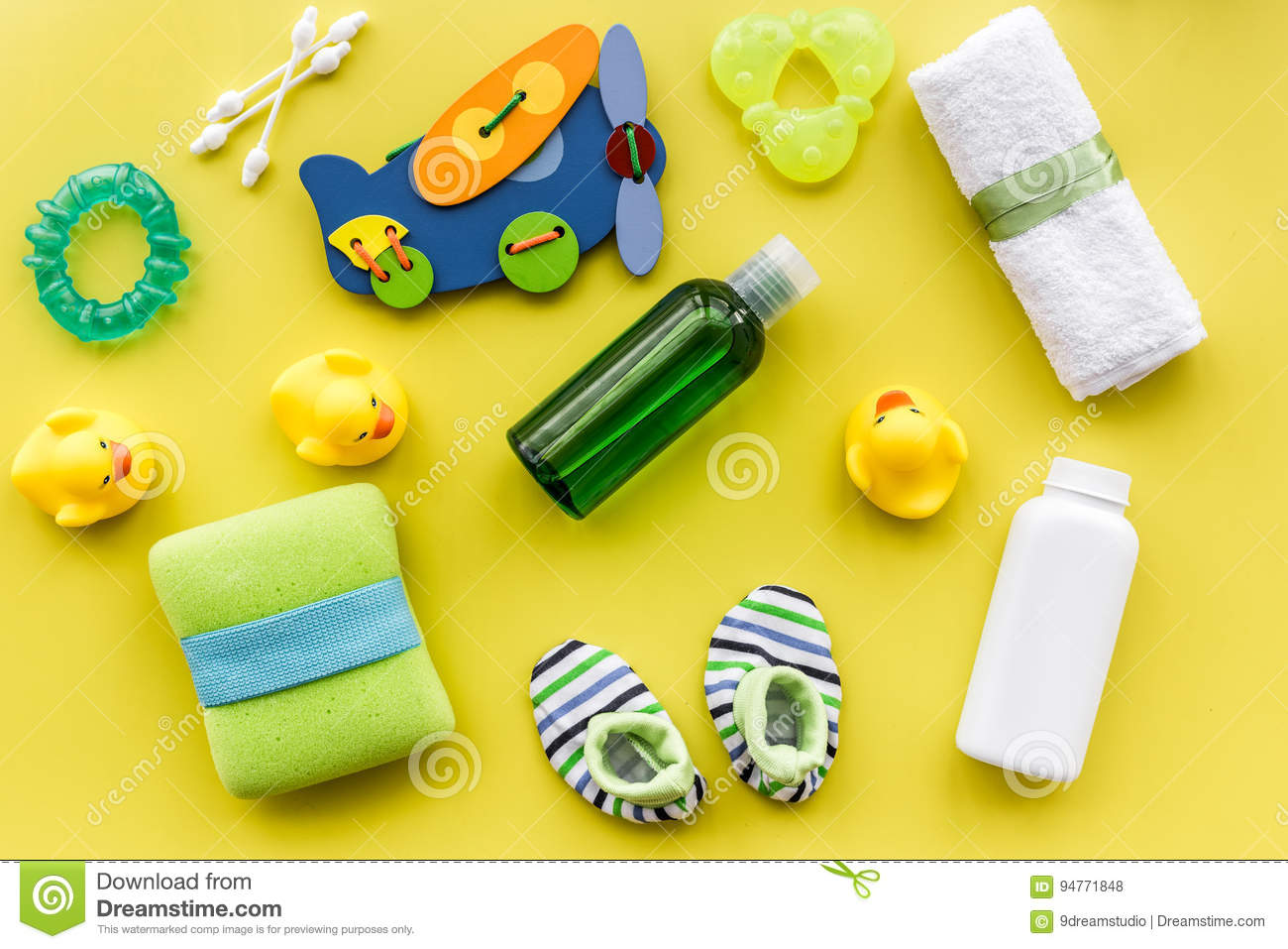 Baby accessories for bath with body cosmetic and ducks on yellow background top view pattern