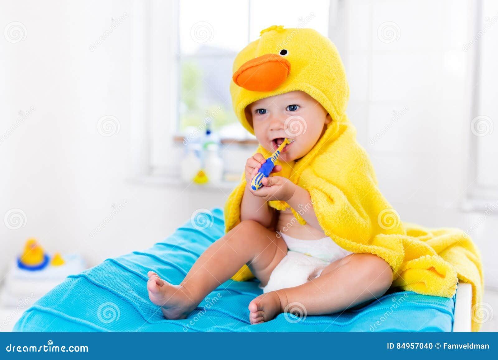 Baby in badhanddoek met tandenborstel