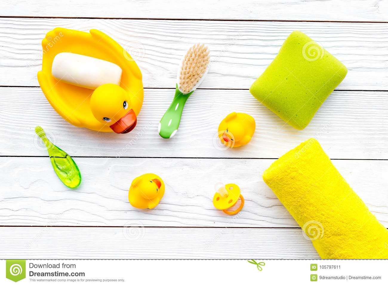 Baby bath set with yellow rubber duck. Soap, sponge, brushes, towel on white wooden background top view