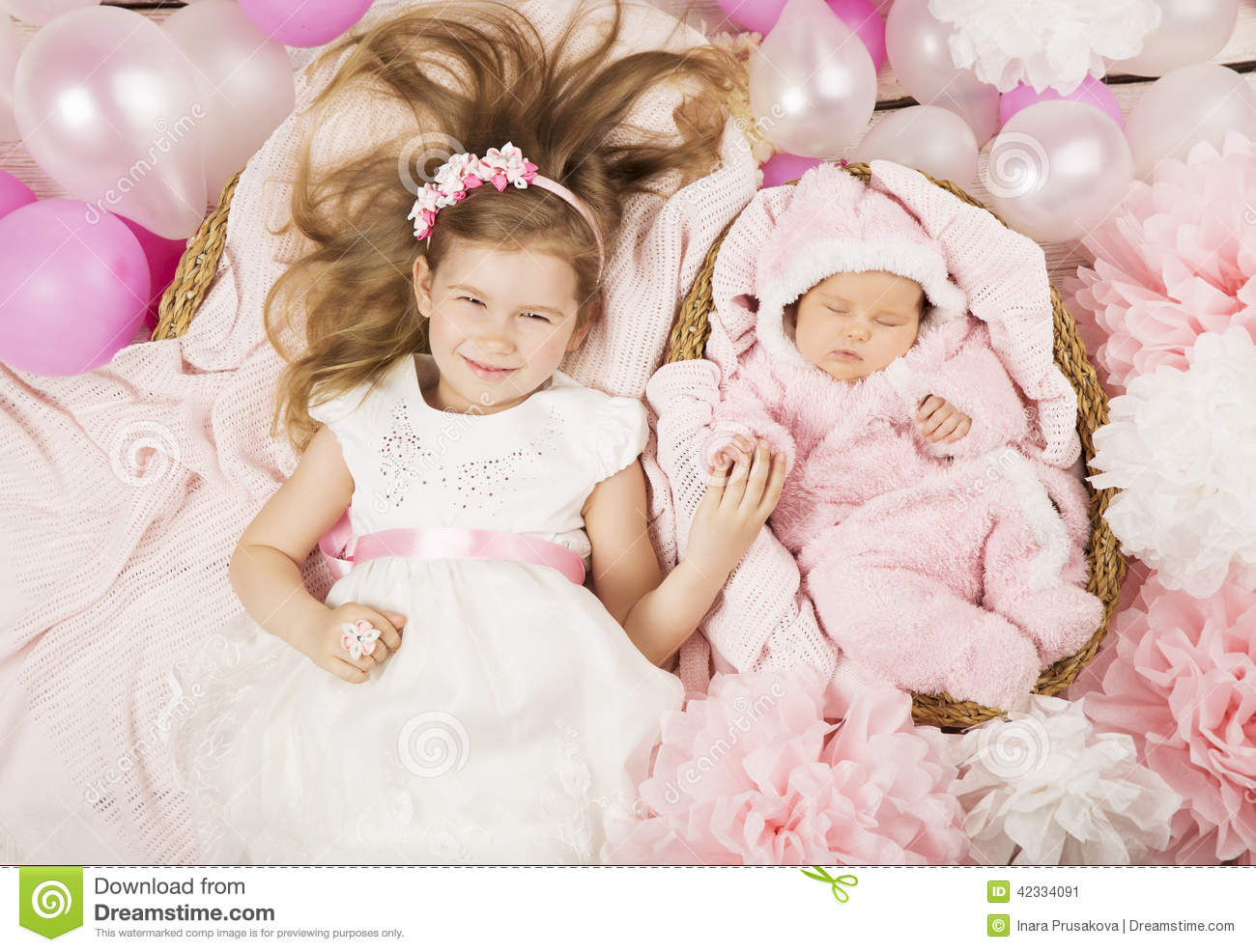 Baby birthday party gifts. Girl holding newborn sister hand. Chi