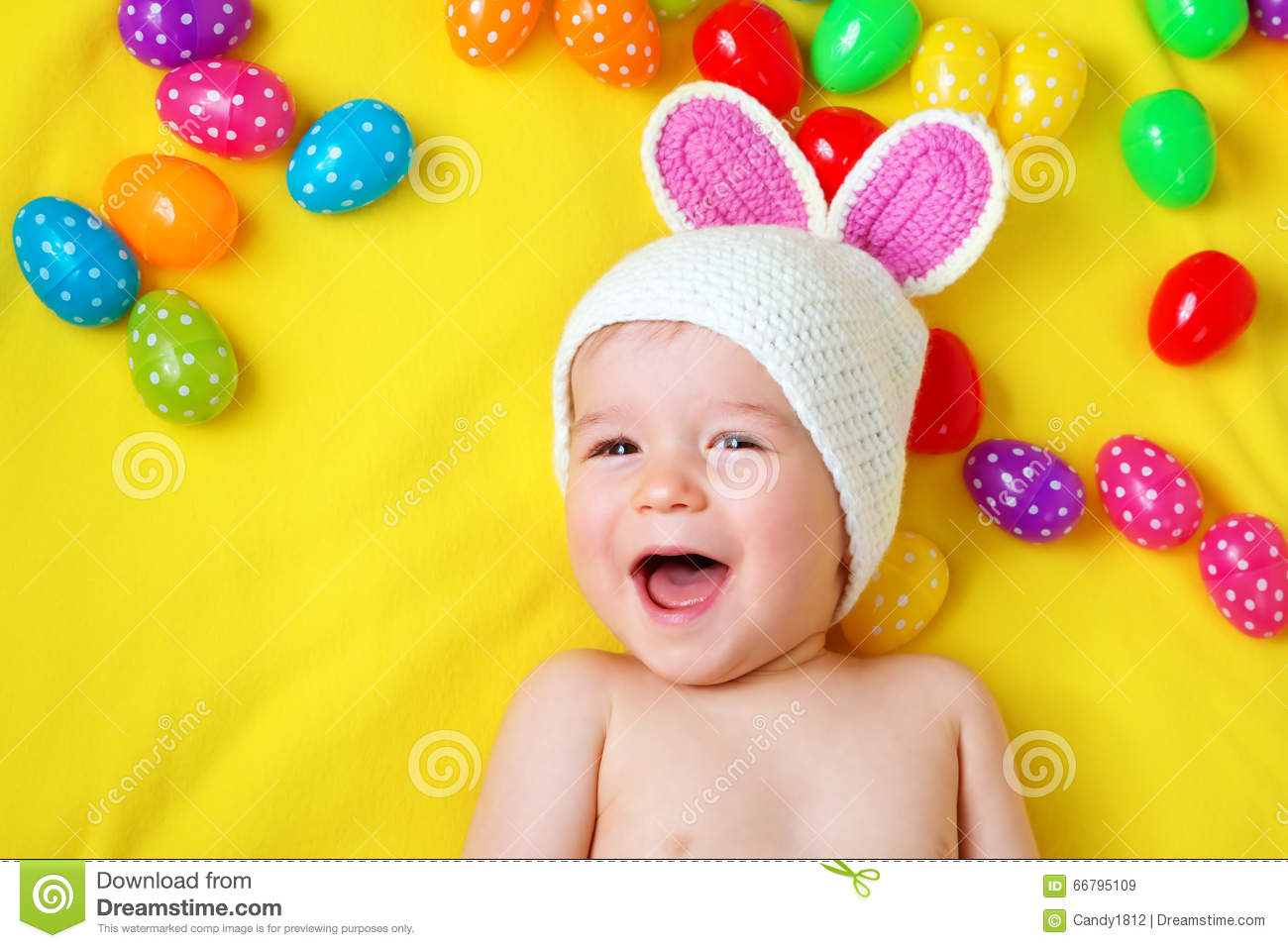 Baby boy in bunny hat lying on yellow blanket with easter eggs