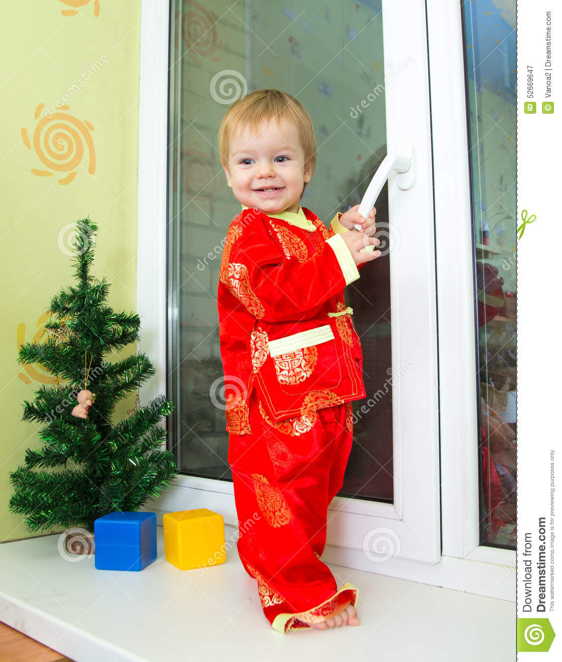 baby boy in chinese new year costume stands on the window sill - Chinese New Year Outfit