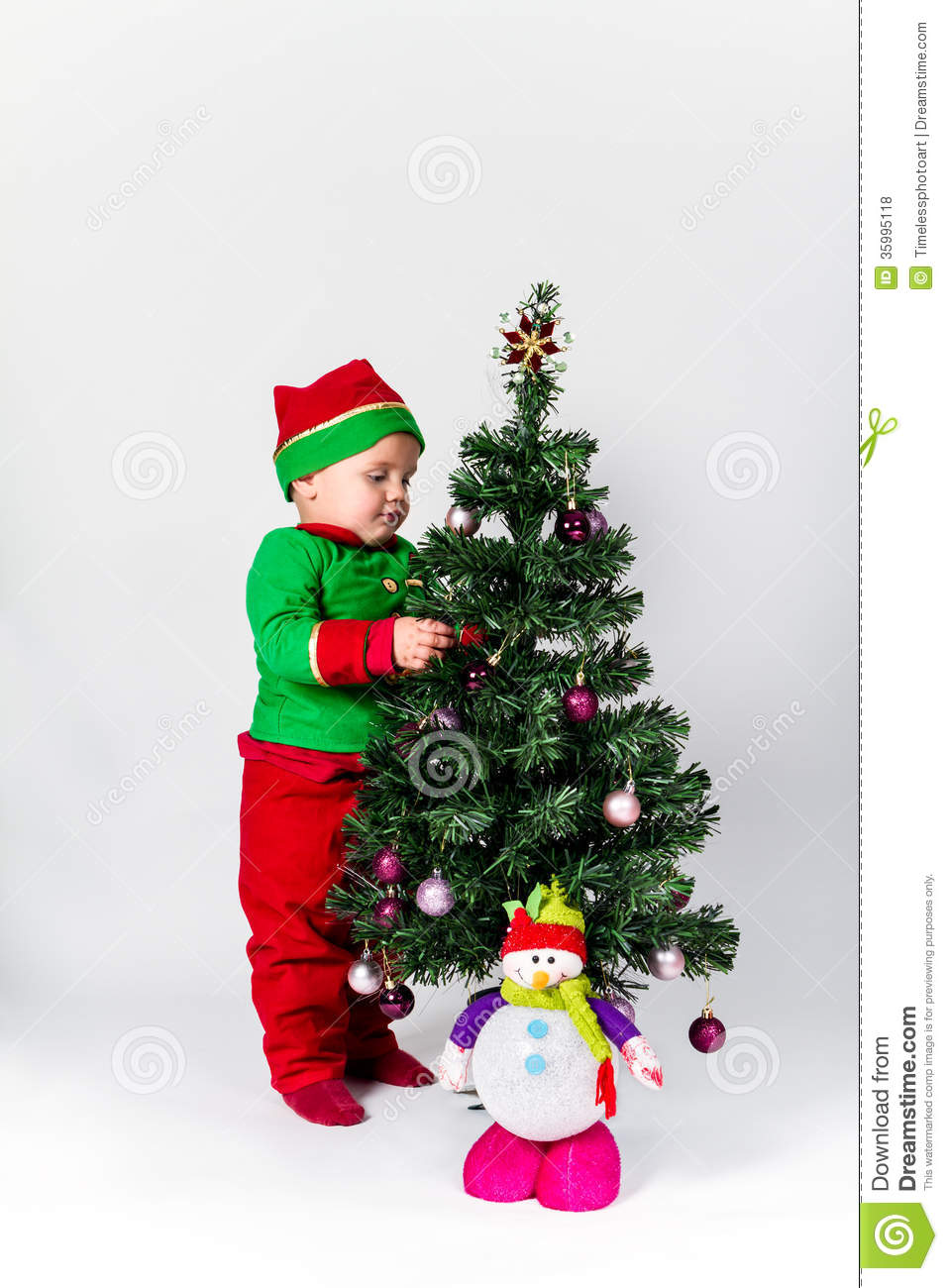 Baby boy dressed as santa 39 s helper decorating christmas for Baby christmas tree decoration