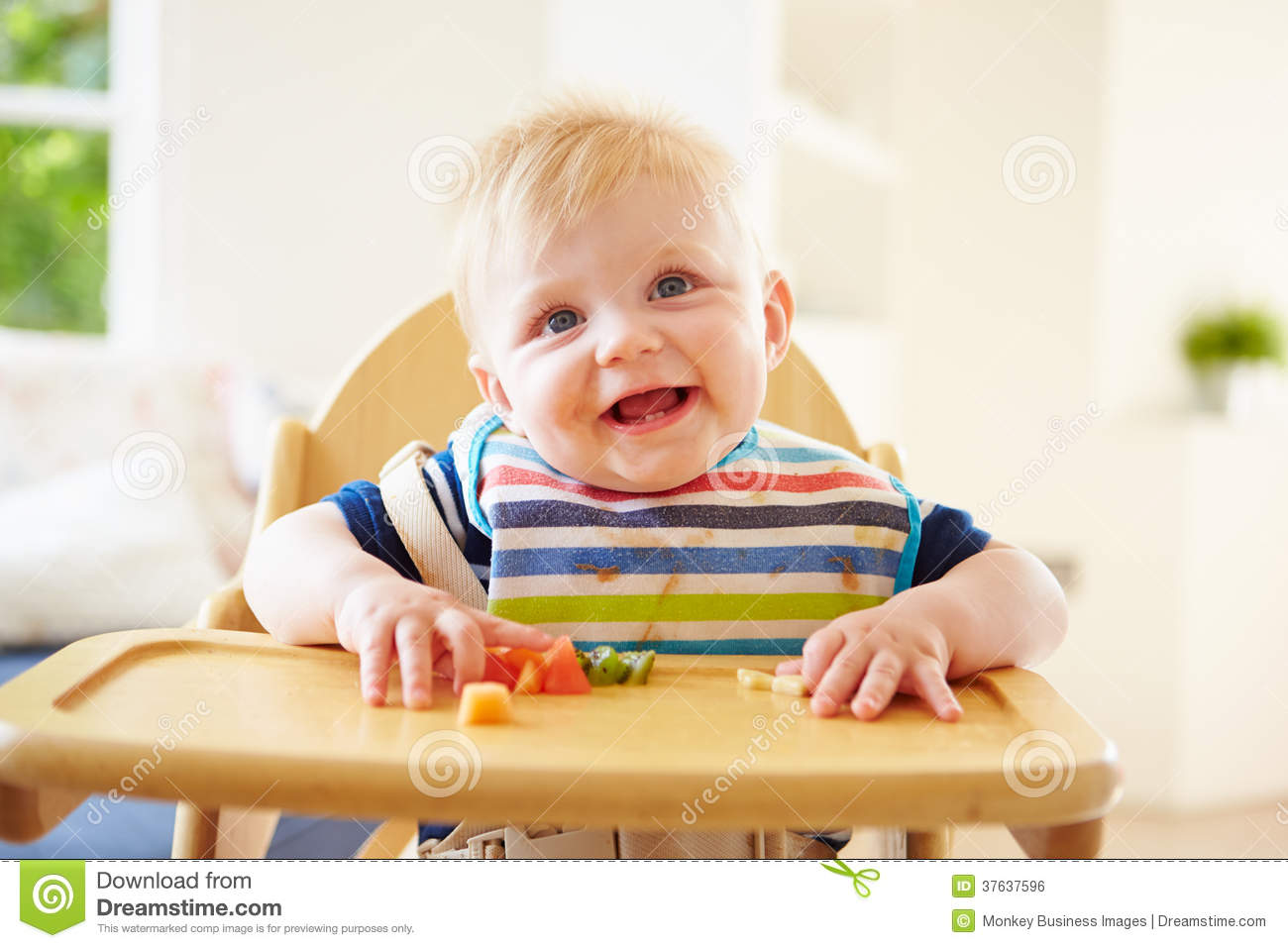 Baby Boy Eating Fruit In High Chair Royalty Free Stock
