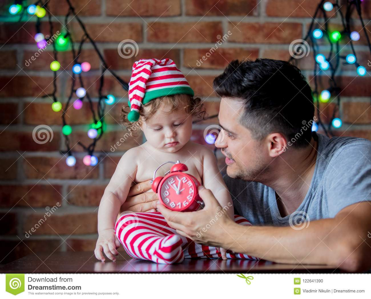 89d1392092d4e Beautiful little baby boy in elf hat and father with alarm clock and fairy  lights on background. Christmas time season image