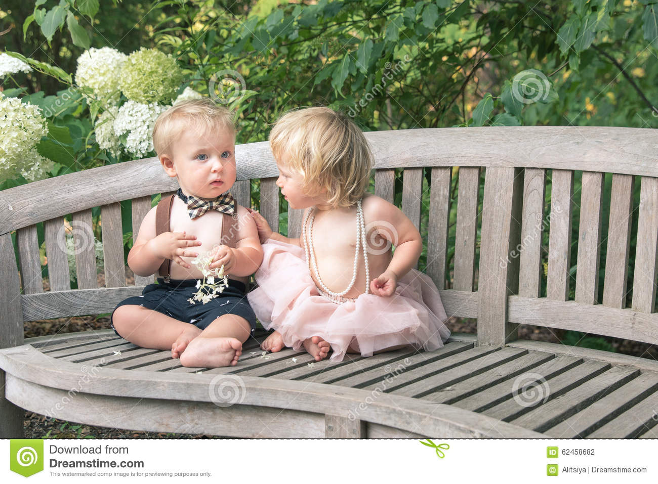 baby boy and girl in formal dress sitting on wooden bench in a