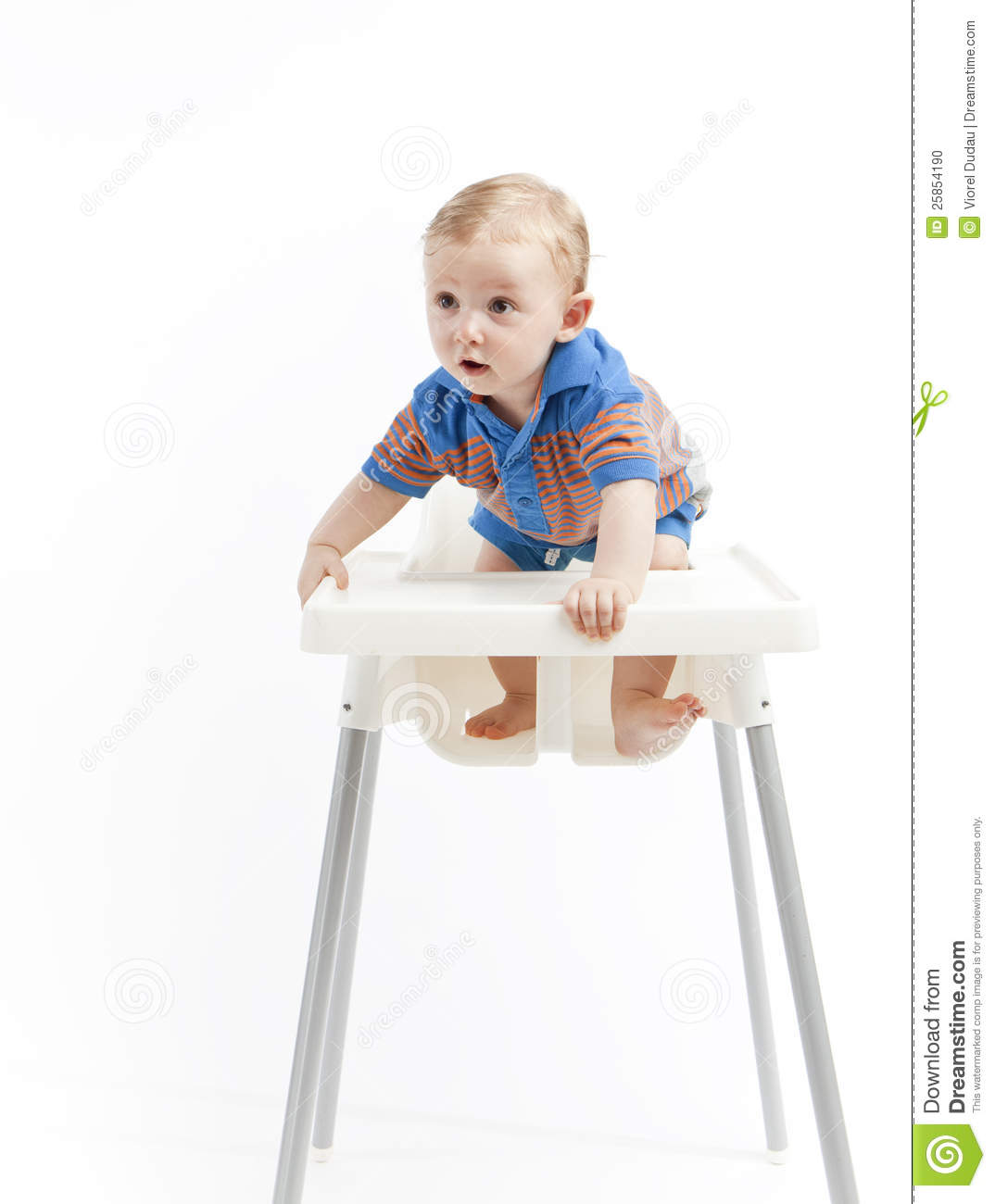 Cute young baby boy climbing in high chair, white studio background.
