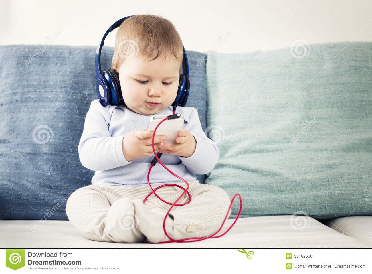 Cute baby boy sitting on sofa and listening music at headphones while ...