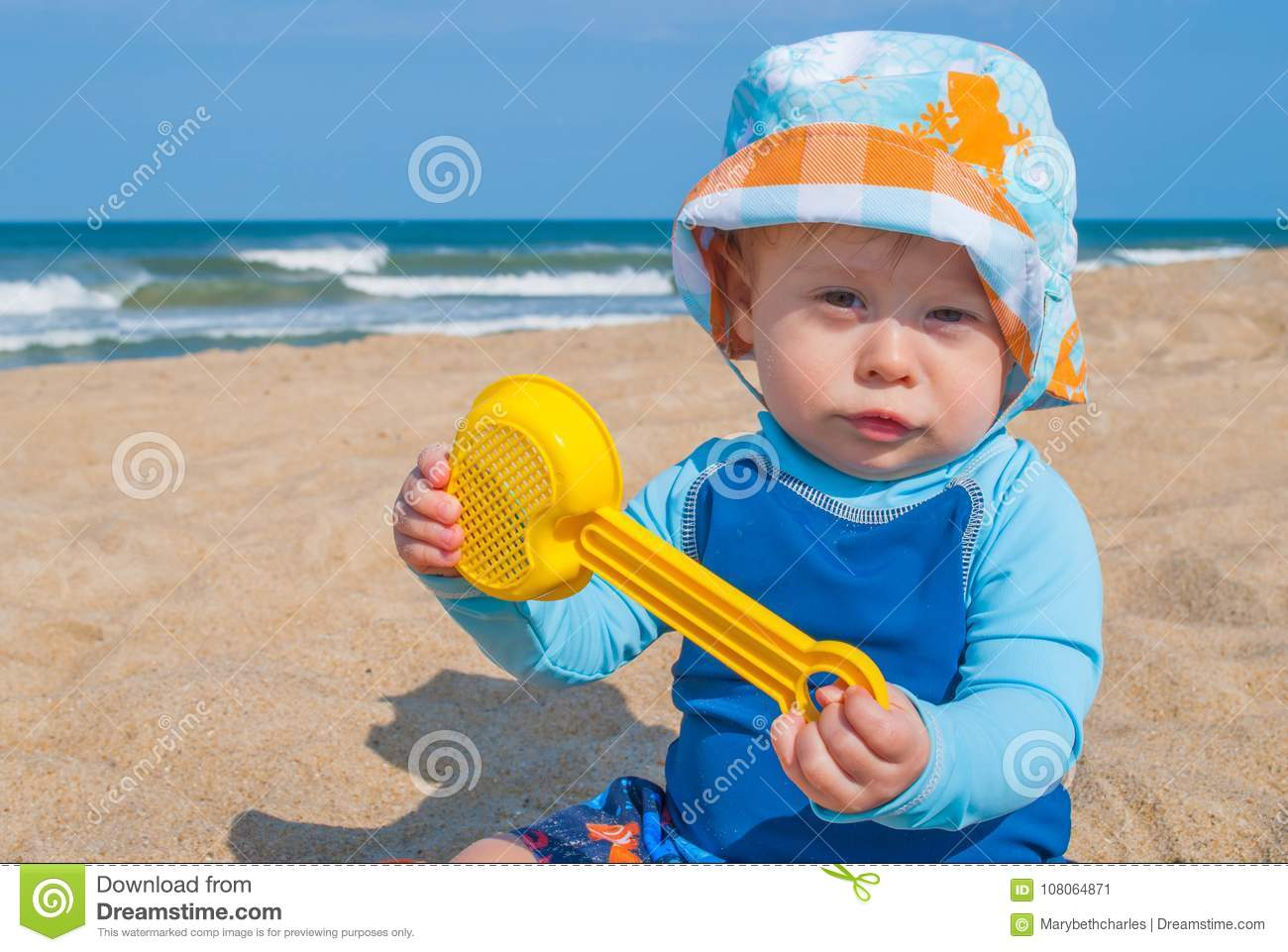 aa80480f7 Baby Boy Wearing Blue Shirt Playing with Toys in the Sand at the Beach
