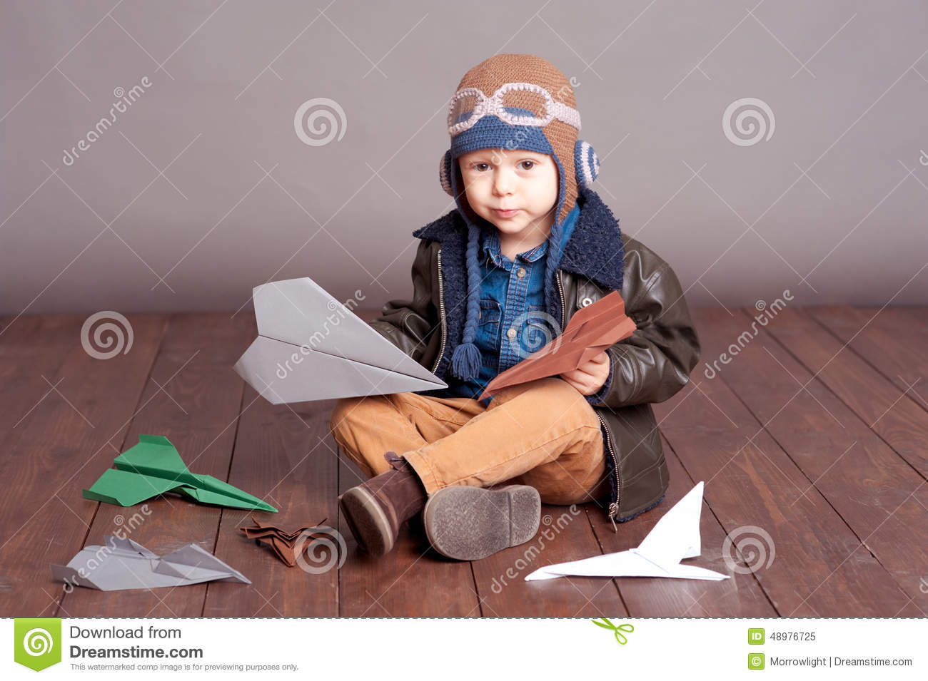 d7410ecf77d Cute baby boy wearing stylish leather jacket and aviator cap over gray.  Playing with paper origami planes in room. Sitting on wooden floor.