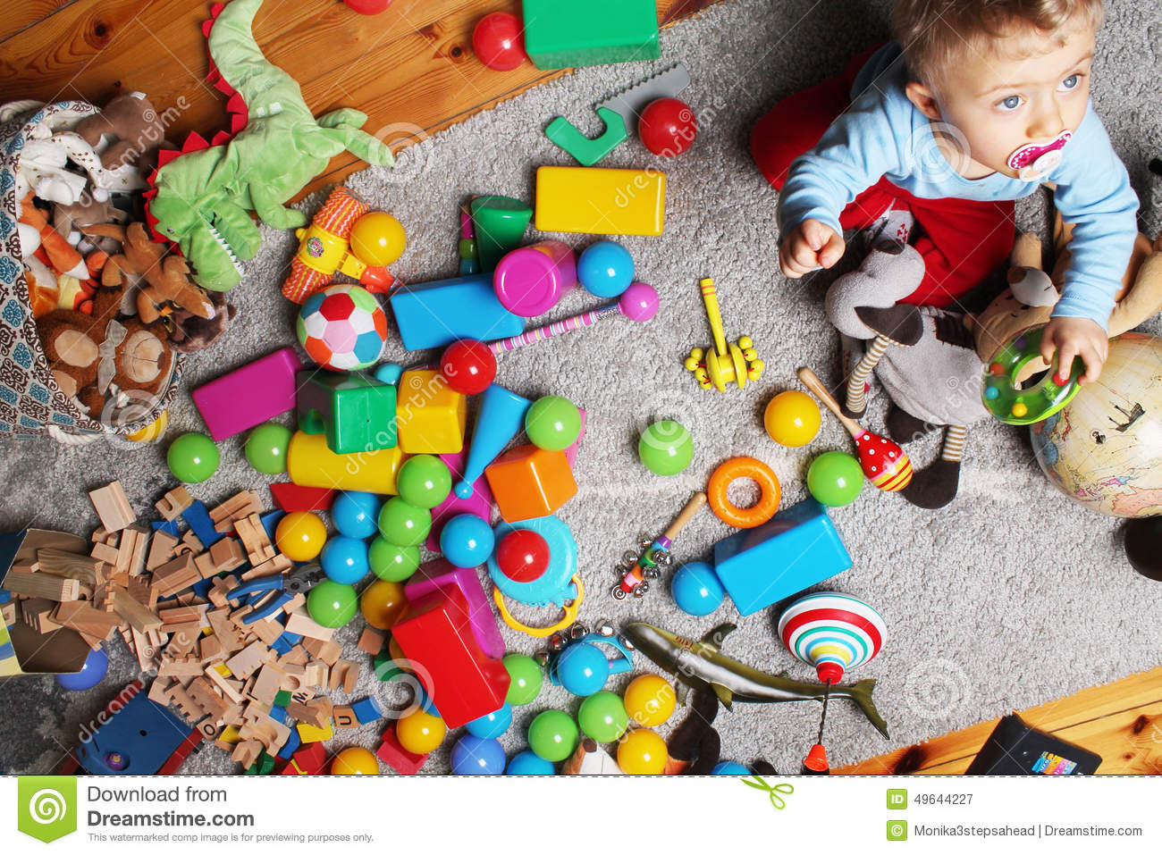 Baby boy playing with his toys on the floor stock photo for On the floor