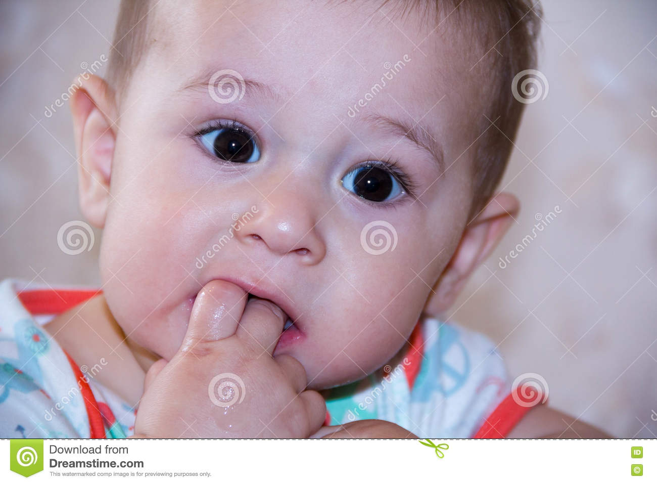 Baby boy plays with fingers in mouth and happy facial expression. Portrait of a crawling smiling. Teething infant playing. Newbor