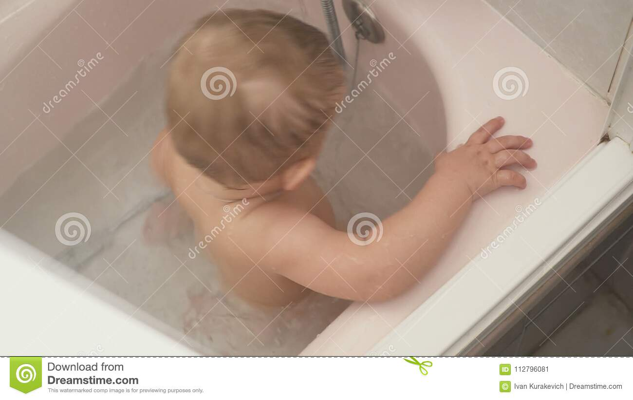 Baby Boy A Shower With Play Water In Bathroom. Baby With Cross ...