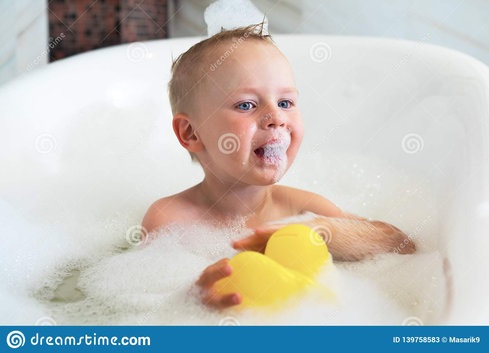 Baby boy sitting in bath with water and foam, cries, eats foam. Smiling kid in bathroom with colorful toy duck. Hygiene and care f